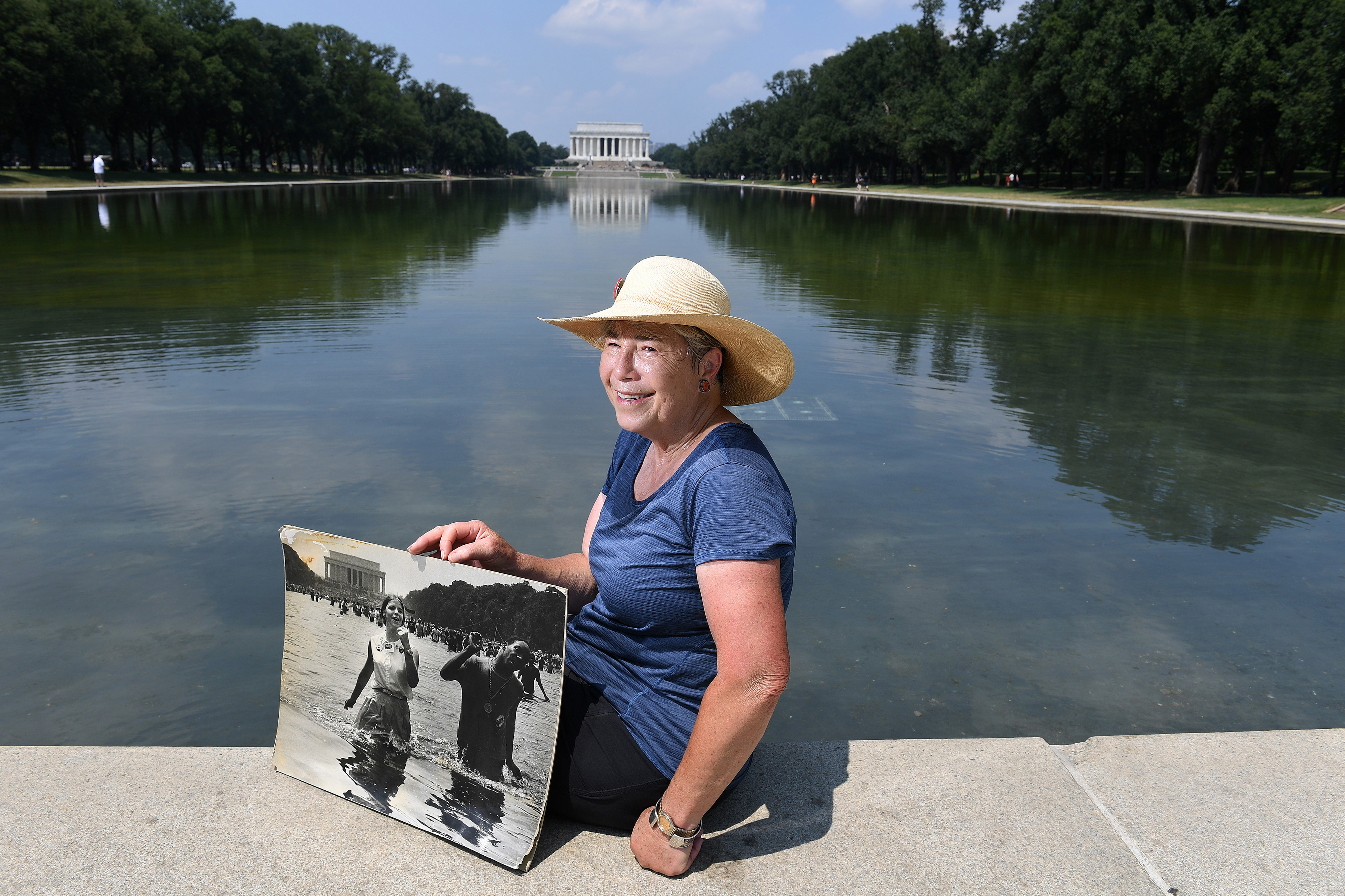 Michele Leimomi Sing Holzman at the Lincoln Memorial Reflecting Pool. Holzman was the subject of a photograph taken by Richard Bensinger at the Lincoln Memorial Reflecting Pool in 1968. She is holding a copy of the original photo. MUST CREDIT: Washington Post photo by Matt McClain
