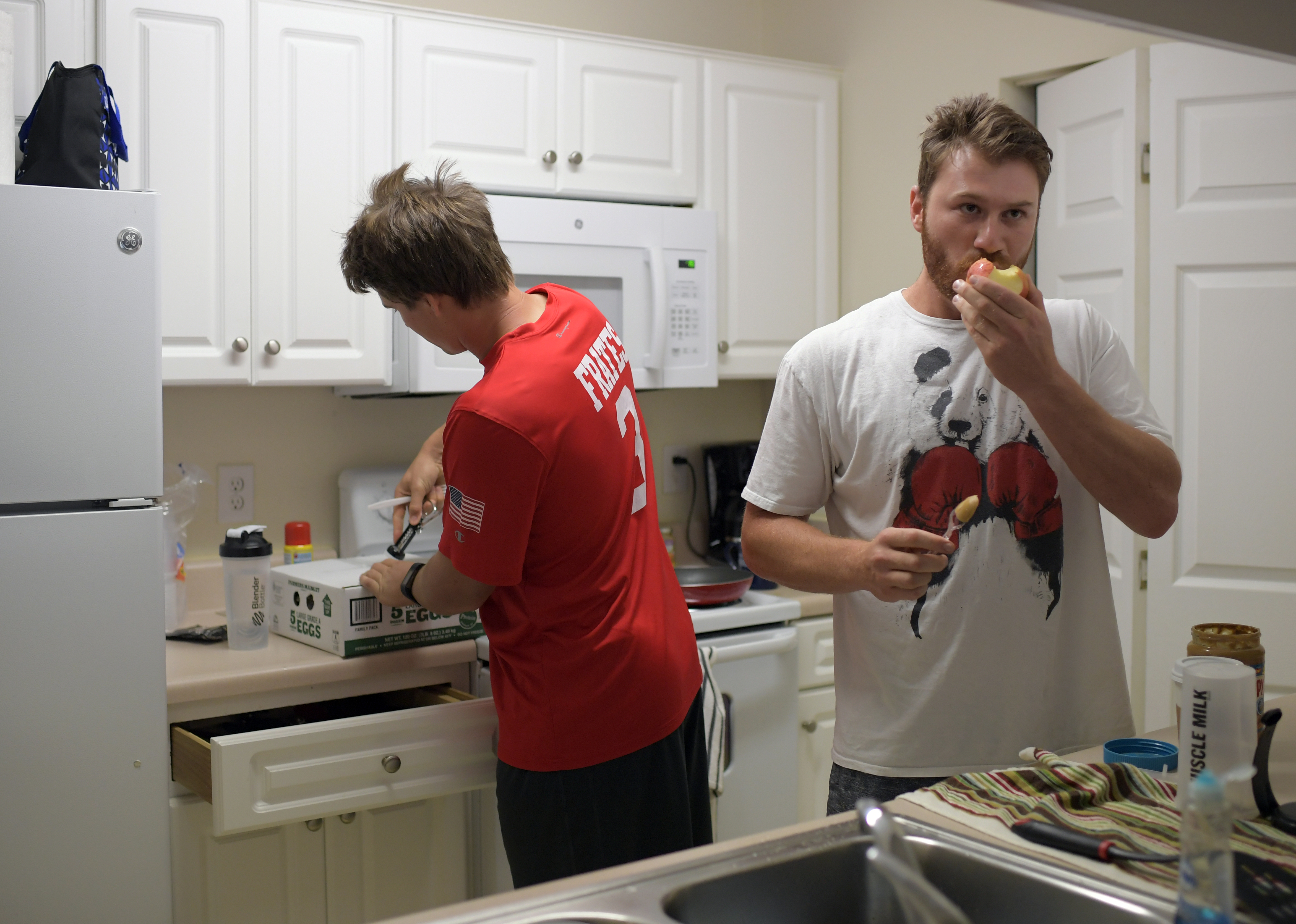Matt Pare' of the single A Augusta GreenJackets ( left) opens a box of eggs in the kitchen as teammate Adam Sonabend eats and apple with peanut butter during breakfast in a an apartment that they share with other teammates in Augusta Ga., on July 15, 2016. MUST CREDIT: Washington Post photo by John McDonnell.