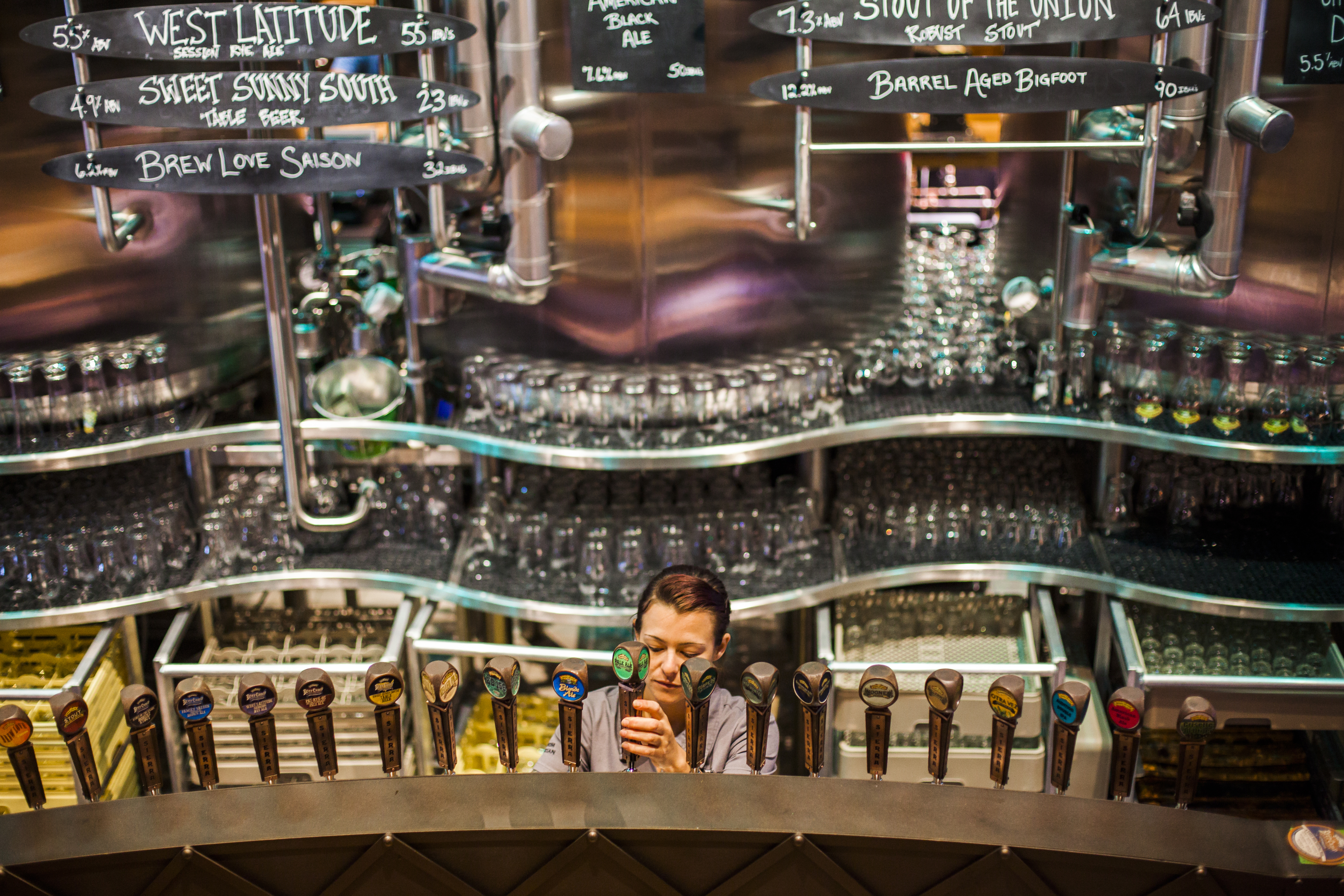 Bartender Morgan Persky pours a pint from one of the 23 beers on tap at Sierra Nevada's taproom in Mills River, North Carolina, on the outskirts of Asheville. Must credit: Photo by Jacob Biba for The Washington Post