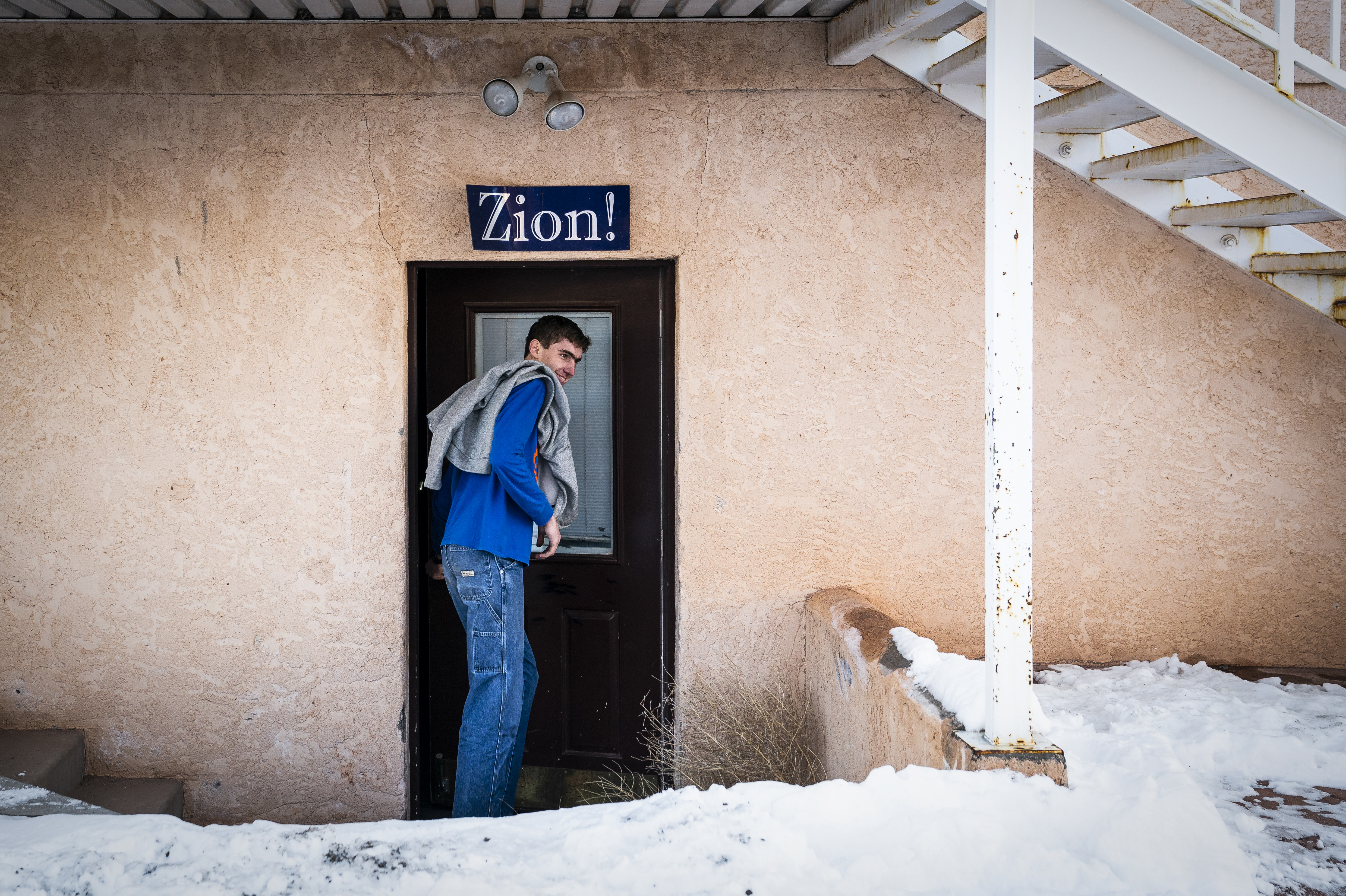James Jeffs goes to his room, framed by a Zion sign, at his family's home. Many people still loyal to the FLDS hang Zion placards over their homes. MUST CREDIT: Washington Post photo by Jabin Botsford.