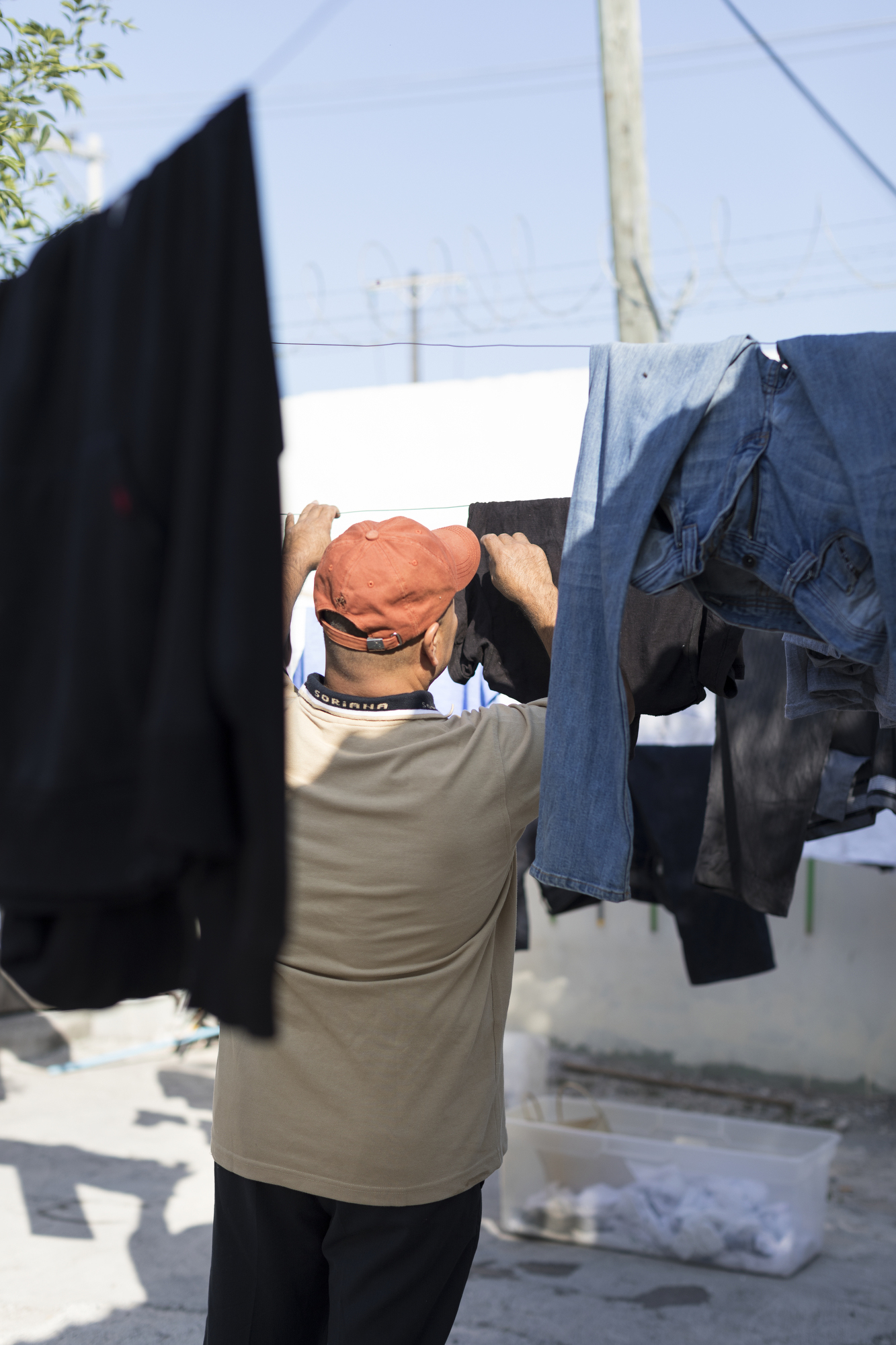 Miguel checks his laundry at the Casa del Migrante in Reynosa. MUST CREDIT: Photo by Alejandro Cartagena for The Washington Post.