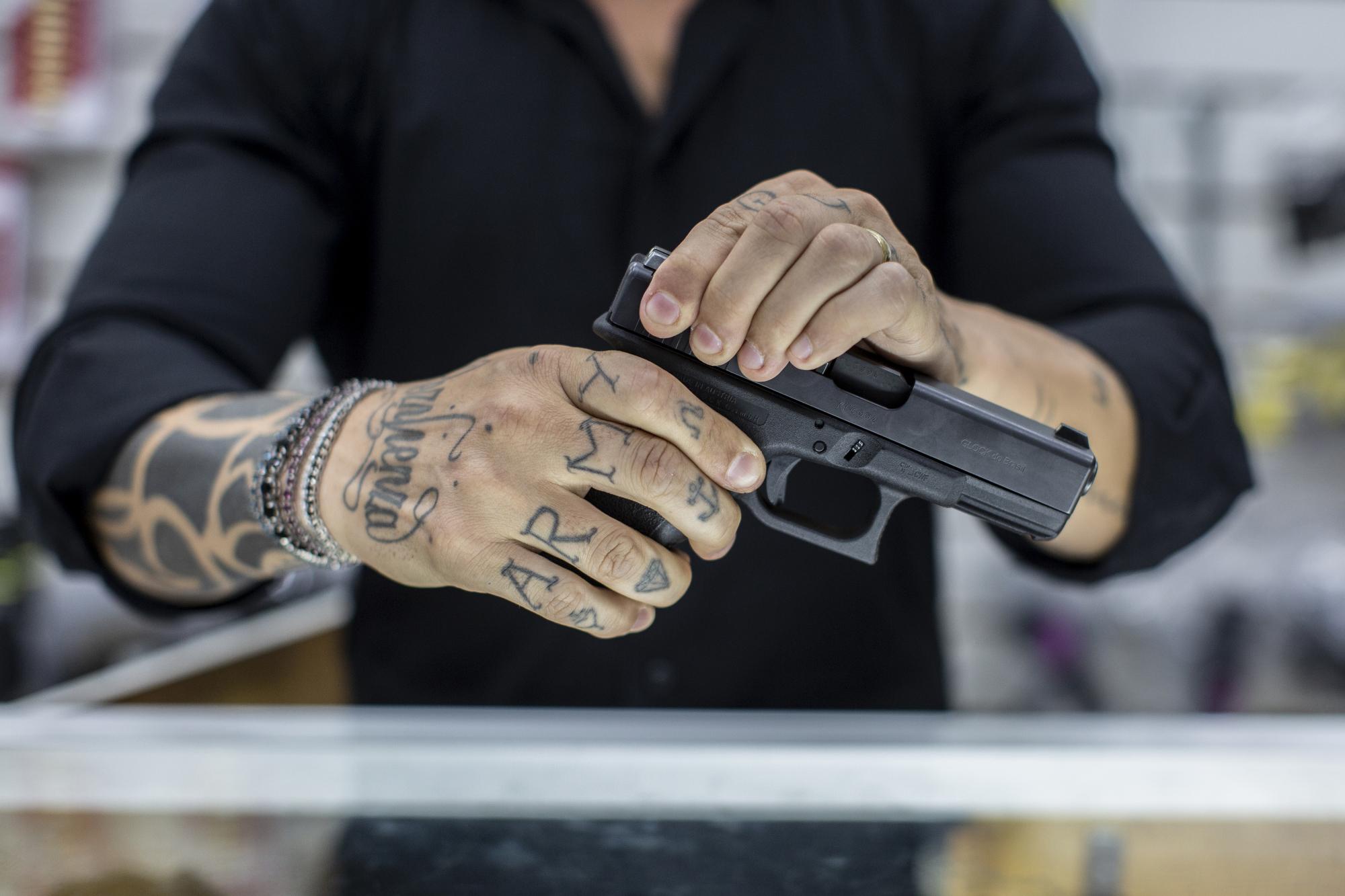 Axl Satier disassembles a handgun in Rio De Janeiro. MUST CREDIT: Photo for The Washington Post by Lianne Milton