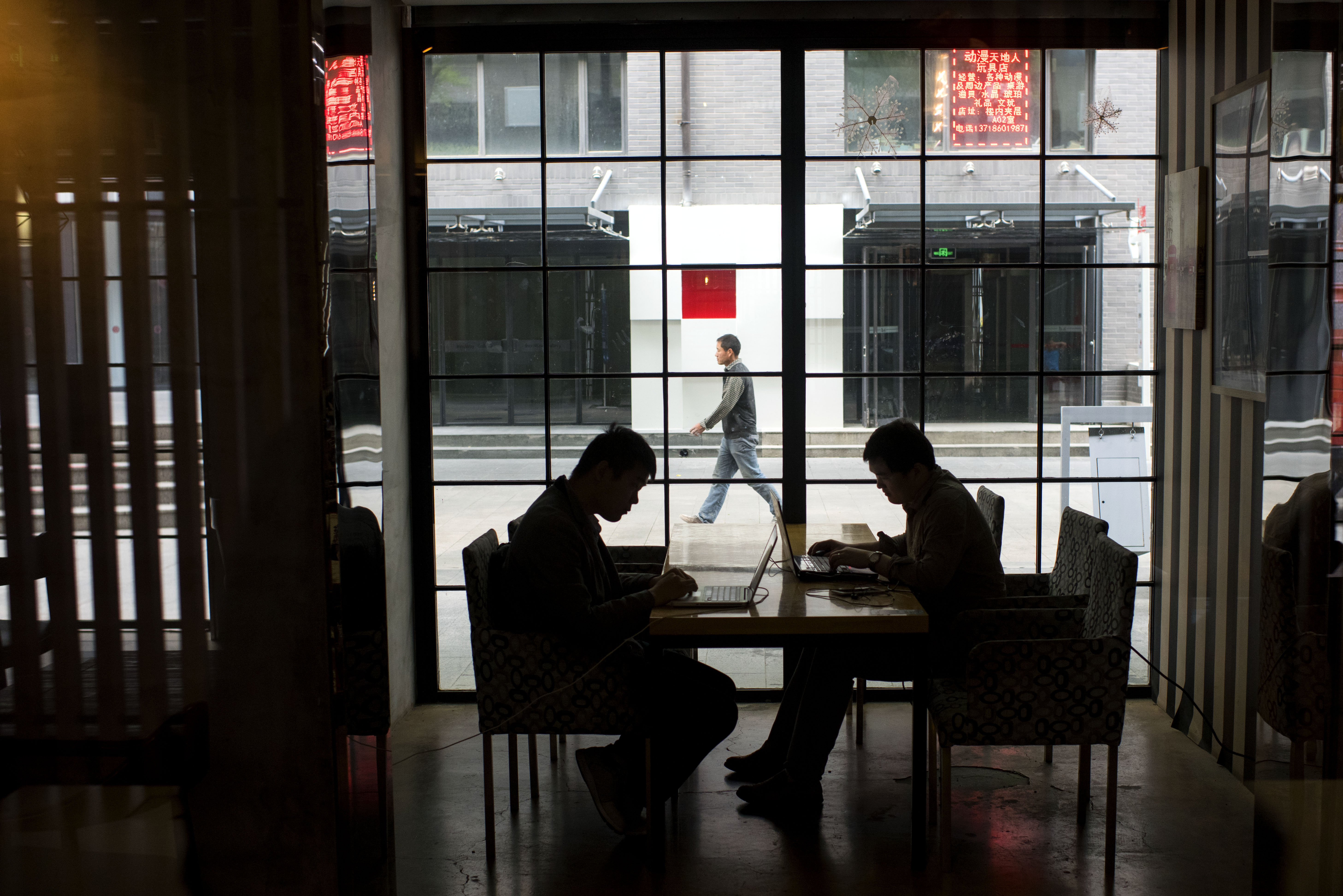 Internet startup employees work on their computers at 3W Coffee in Beijing earlier this year. Mobile device usage and e-commerce are in wide use in China, and now the Communist Party wants to compile a