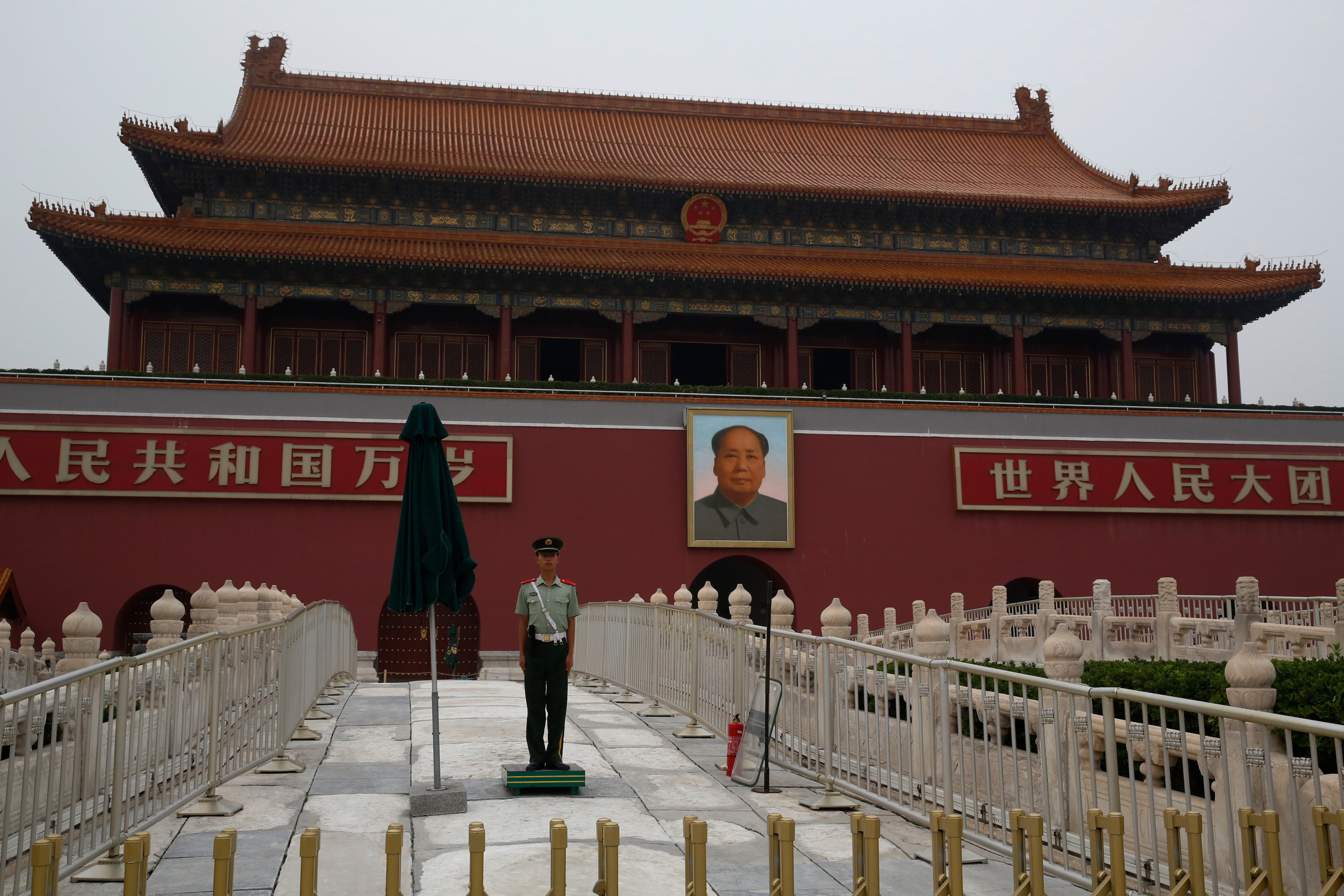 A member of the Chinese People's Liberation Army stands guard in front of a portrait of former Chinese leader Mao Zedong in Tiananmen Square in Beijing on July 28, 2016. MUST CREDIT: Bloomberg photo by Luke MacGregor.