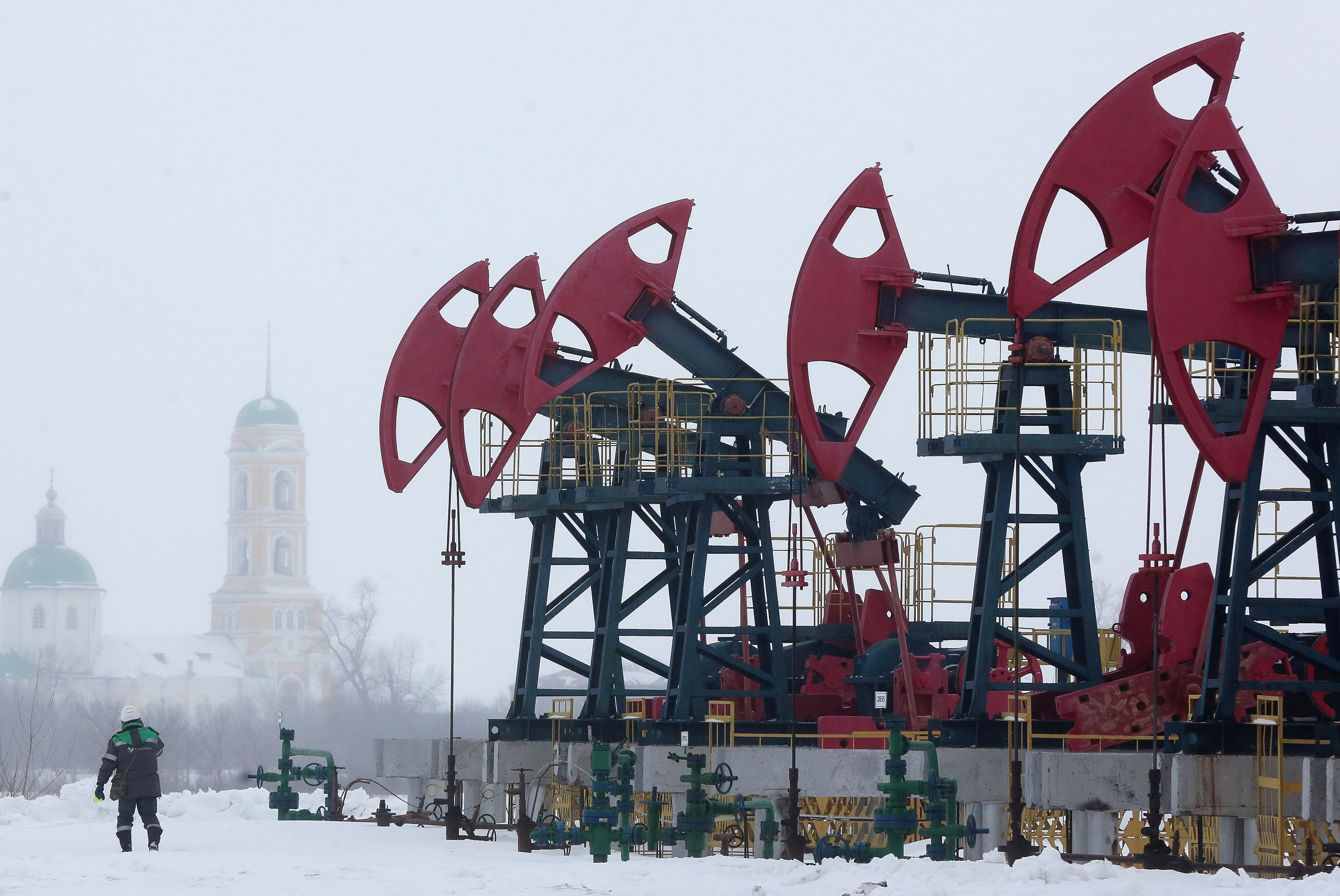A worker passes a line of oil pumping jacks outside the village of Nikolo-Beryozovka near Neftekamsk, Russia, on March 3, 2016. MUST CREDIT: Bloomberg photo by Andrey Rudakov.