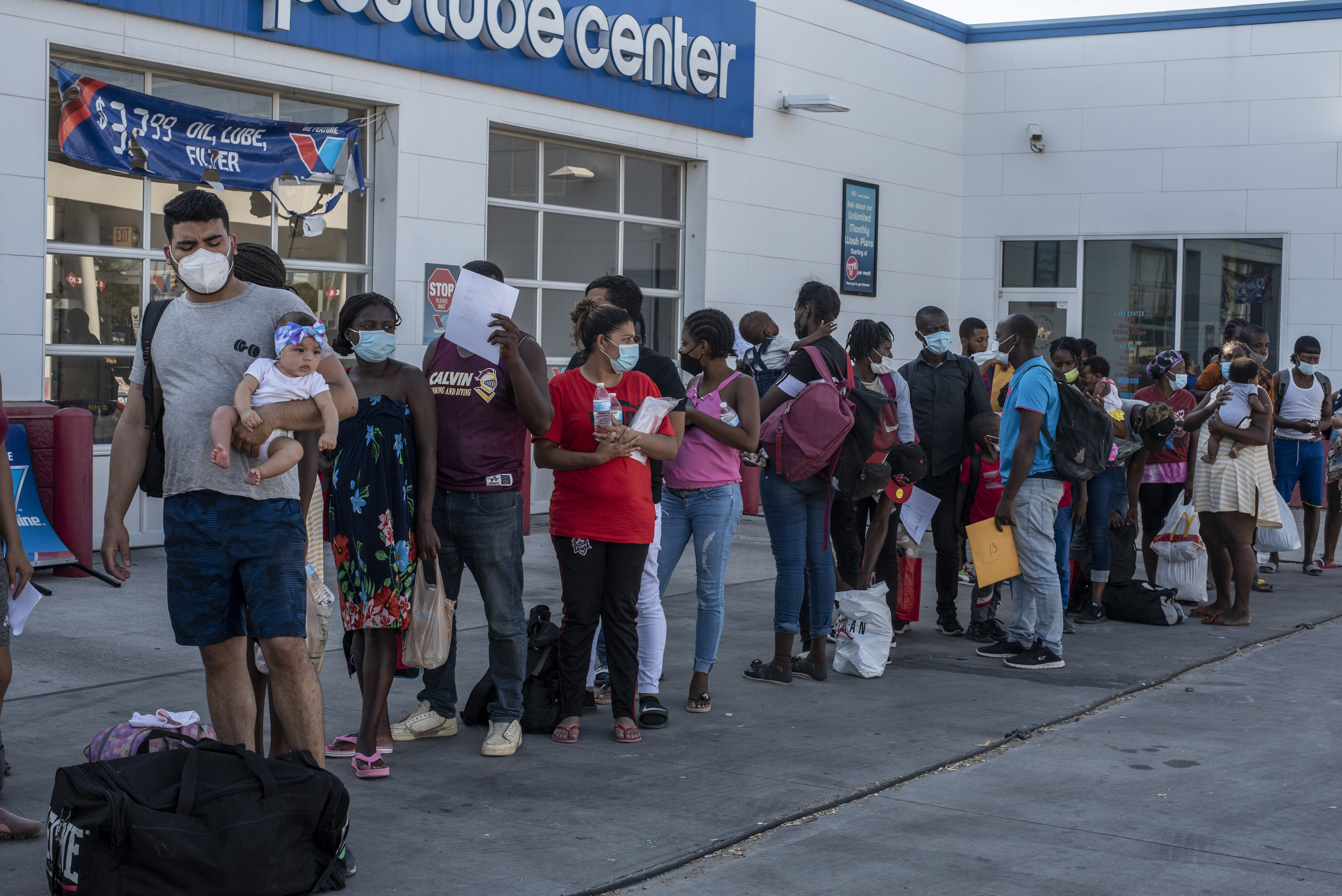Migrant families wait at a bus stop Sunday in Del Rio, Texas, where thousands of migrants, mostly from Haiti, have recently gathered amid food shortages and deteriorating sanitary conditions. MUST CREDIT: Photo by Sergio Flores for The Washington Post