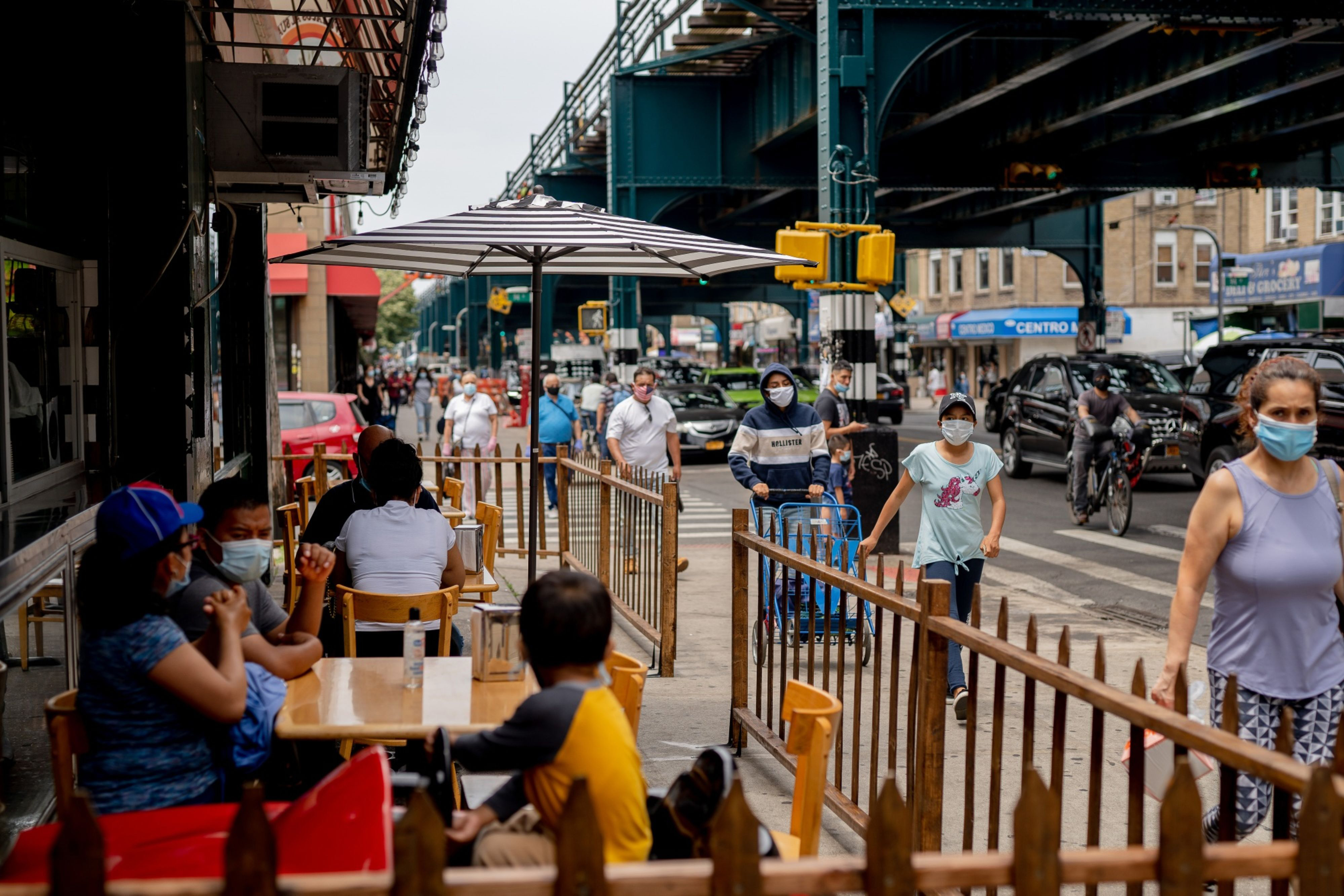 Pedestrians wearing protective masks pass in front of customers sitting outside to eat at a restaurant in the Corona neighborhood in the Queens borough of New York on June 27, 2020. MUST CREDIT: Bloomberg photo by Amir Hamja.