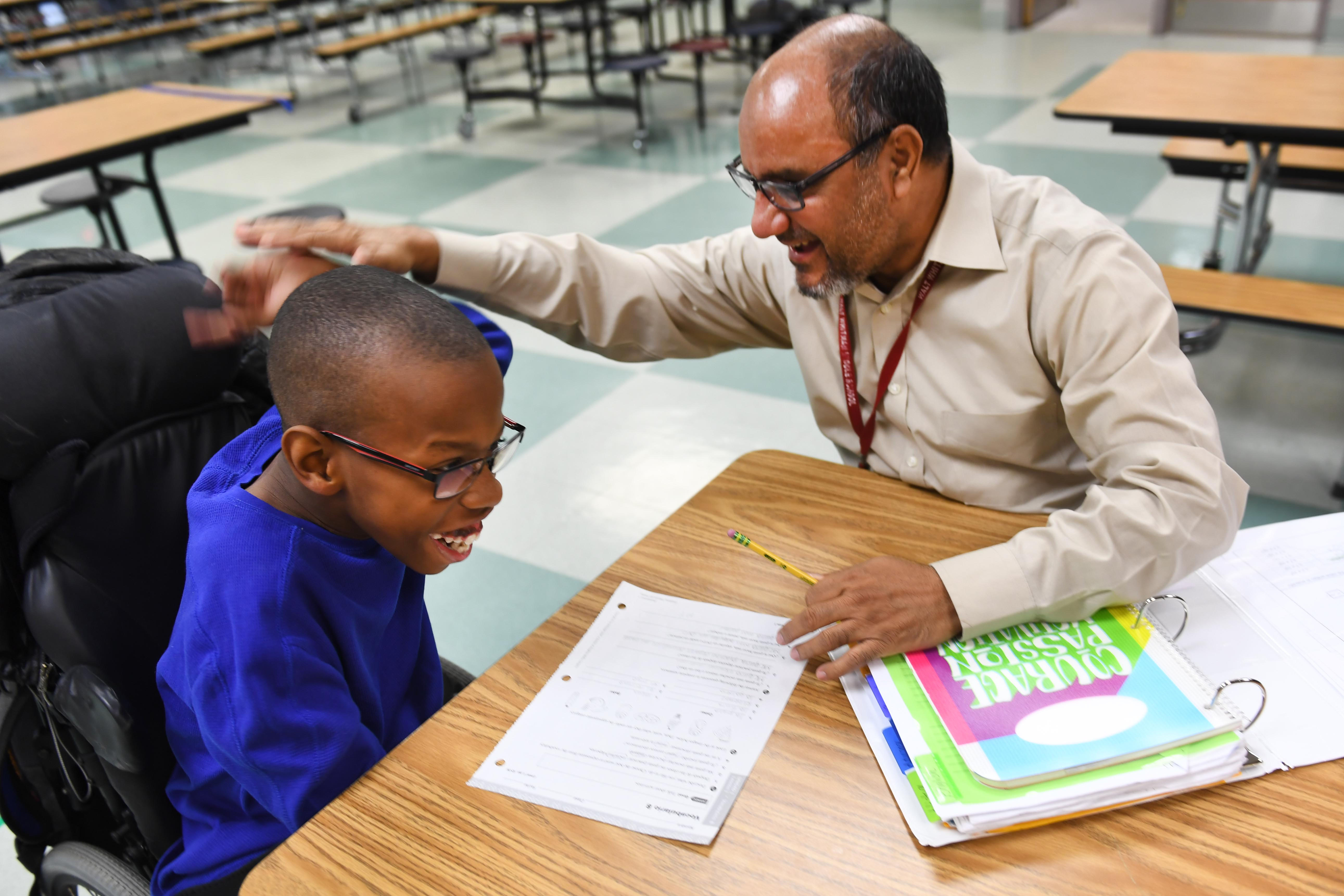 Abid Mohammad, public health training assistant at Walt Whitman Middle School in Alexandria, Virginia, gives a high-five to M.J. Arnold, who successfully completed his Spanish homework worksheet during an after-school program lsat month. MUST CREDIT: Washington Post photo by Katherine Frey.