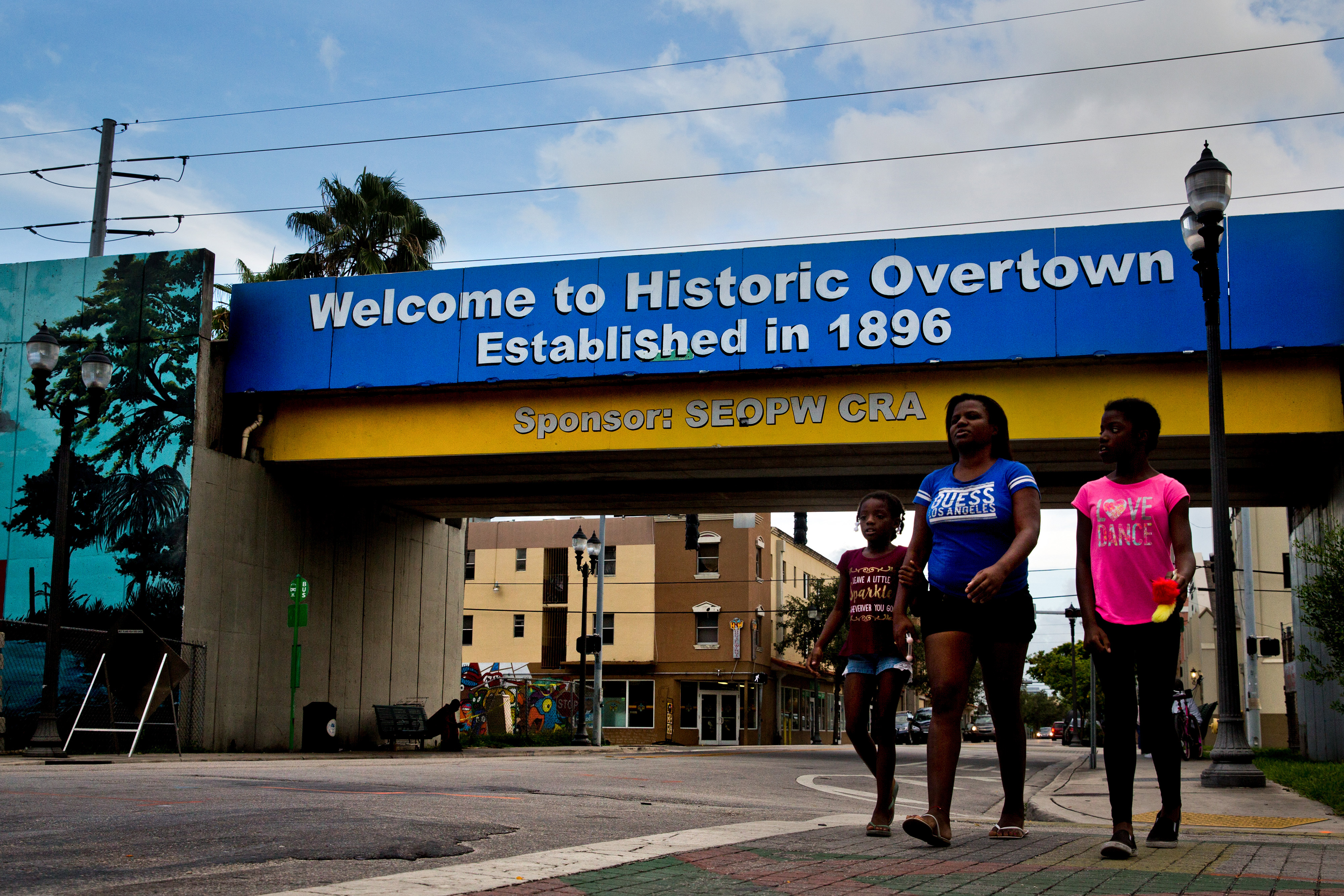 People walk through Miami's Overtown neighborhood on Wednesday. MUST CREDIT: Photo by Scott McIntyre for The Washington Post.
