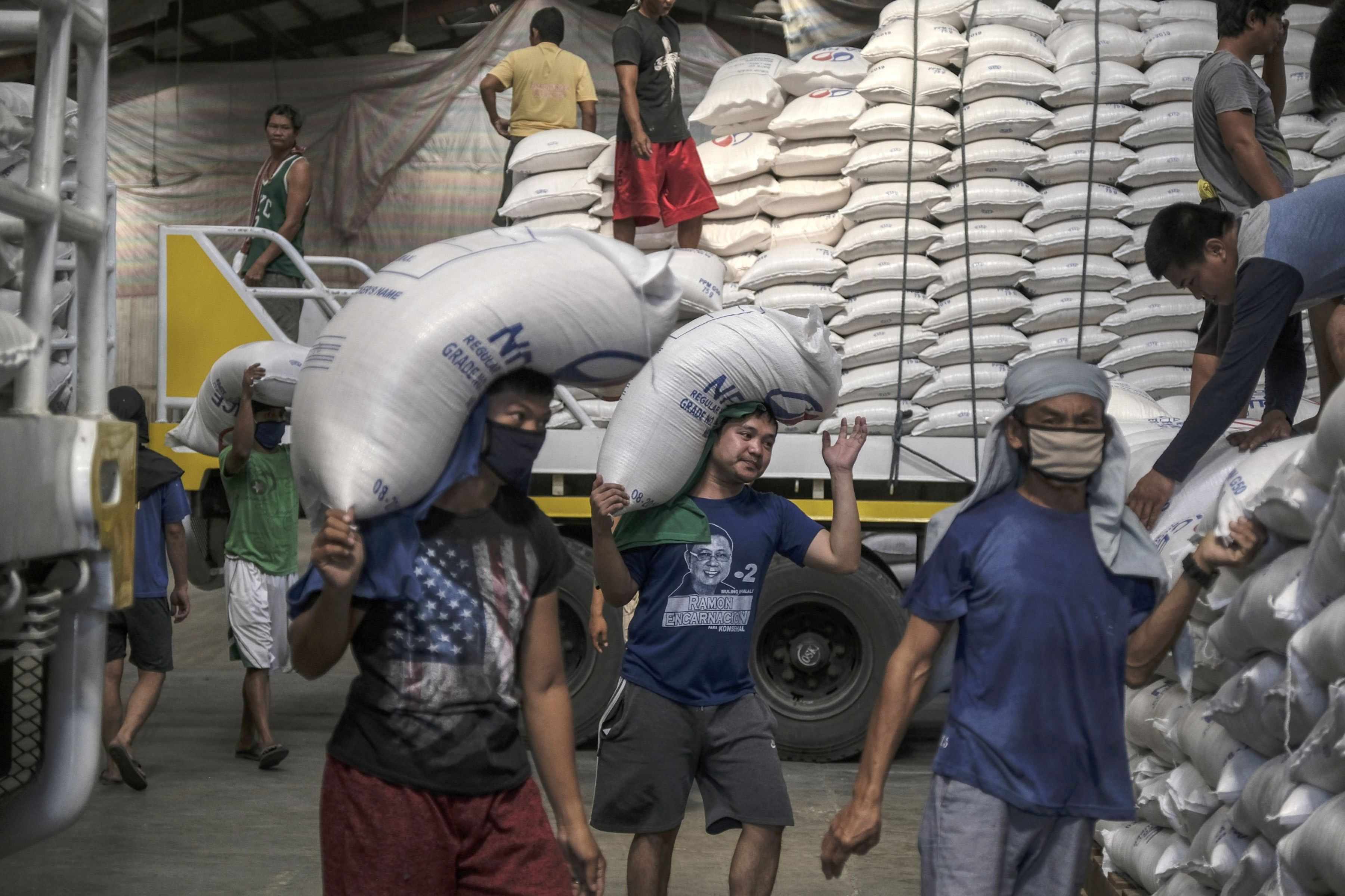 Workers carry sacks of rice inside a National Food Authority warehouse in Valenzuela, Philippines, on March 26, 2020. MUST CREDIT: Bloomberg photo by Veejay Villafranca.