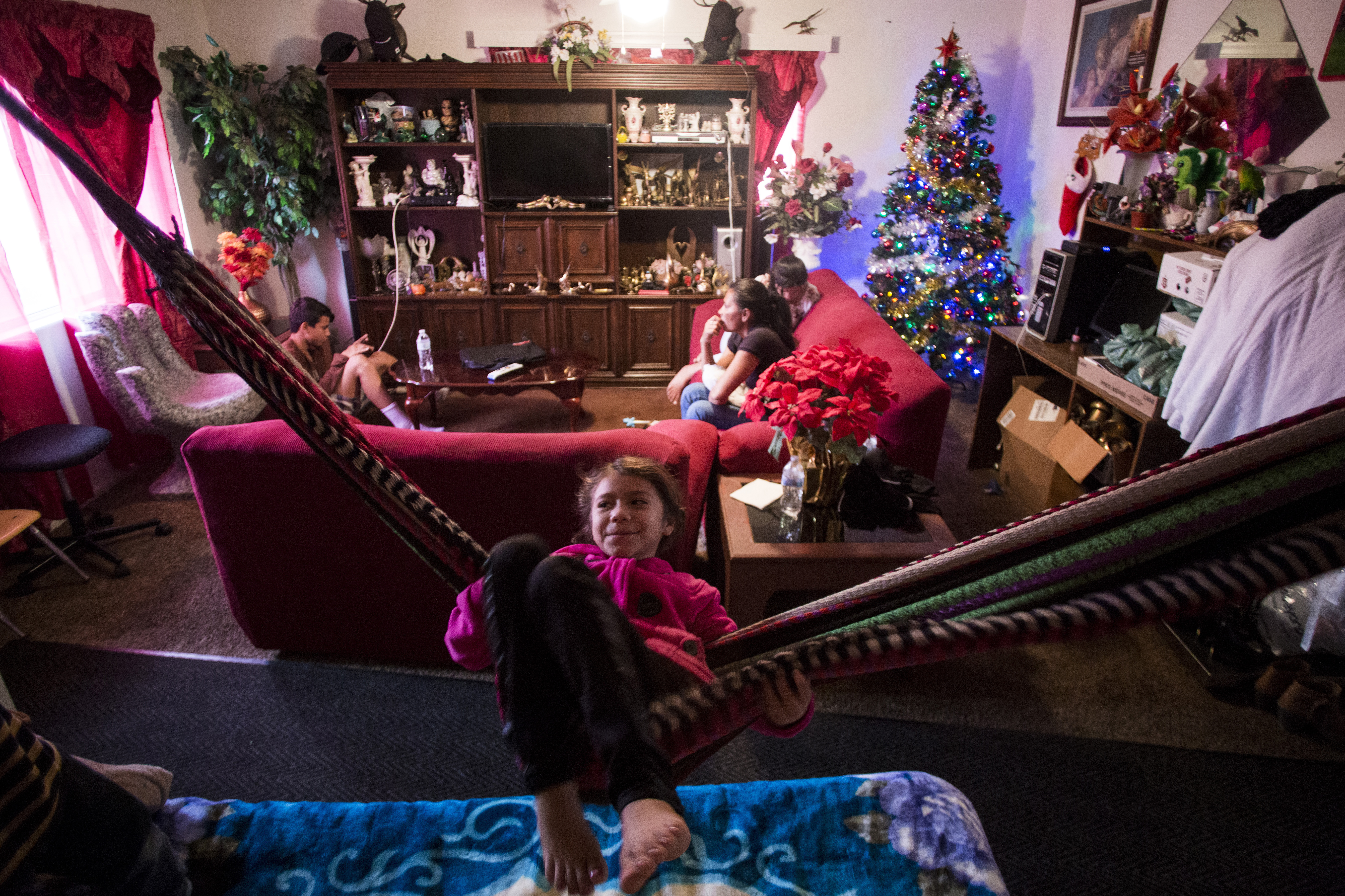 Elen Euceda, 8, plays on the hammock temporarily set up in the living room of her aunt's home in Bakersfield, Calif. MUST CREDIT: Photo for The Washington Post by Jenna Schoenefeld