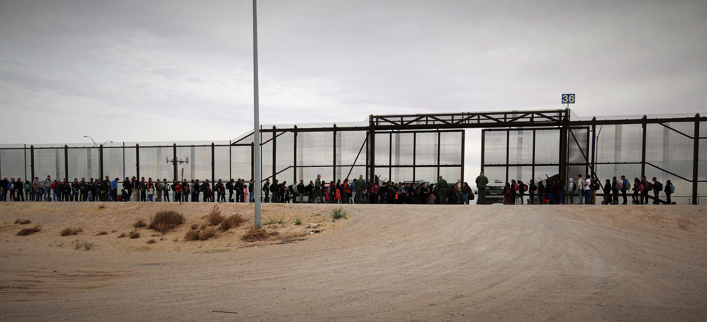 Migrants are shown lined up outside the wall in El Paso, Texas, on March 7. This group of 127 Guatemalan migrants had waded through the river to turn themselves in to U.S. agents, the first step in initiating the asylum process. MUST CREDIT: Photo courtesy of the U.S. Customs and Border Protection.
