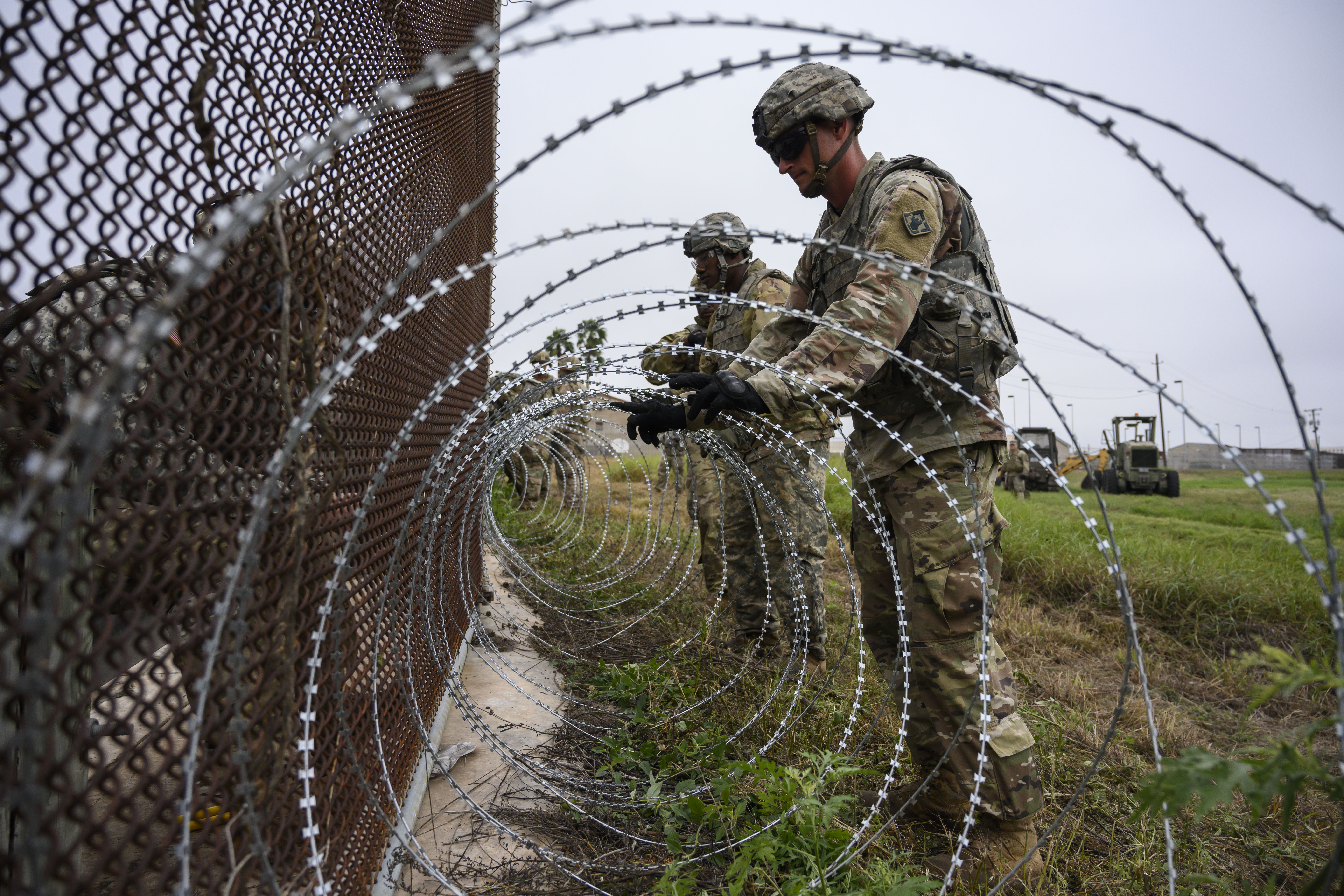 Soldiers put up concertina wire on a border fence near the Brownsville and Matamoros Express International Bridge in Brownsville, Texas on Nov. 11, 2018. MUST CREDIT: Washington Post photo by Calla Kessler