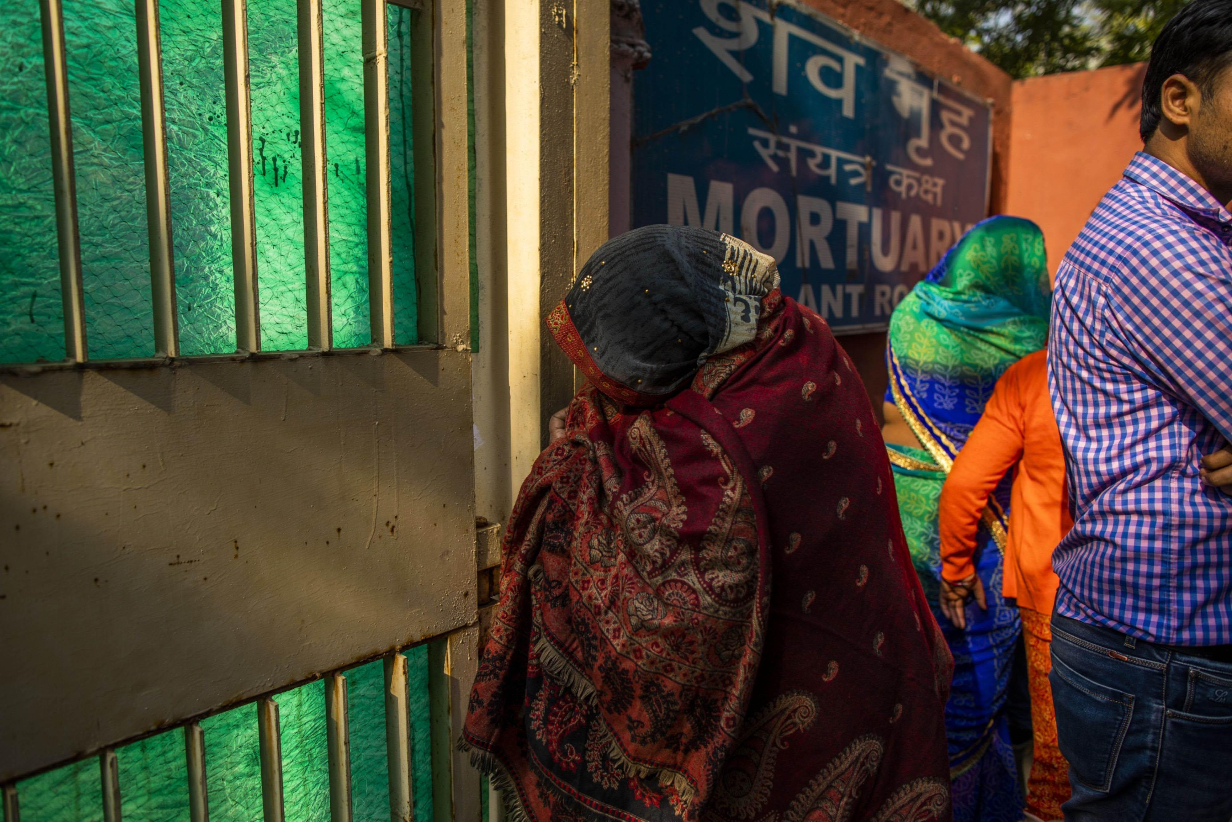 A woman peeks through the gate to the mortuary at the Guru Teg Bahadur Hospital in Delhi, India, on Feb. 26, 2020. MUST CREDIT: Bloomberg photo by Prashanth Vishwanathan.