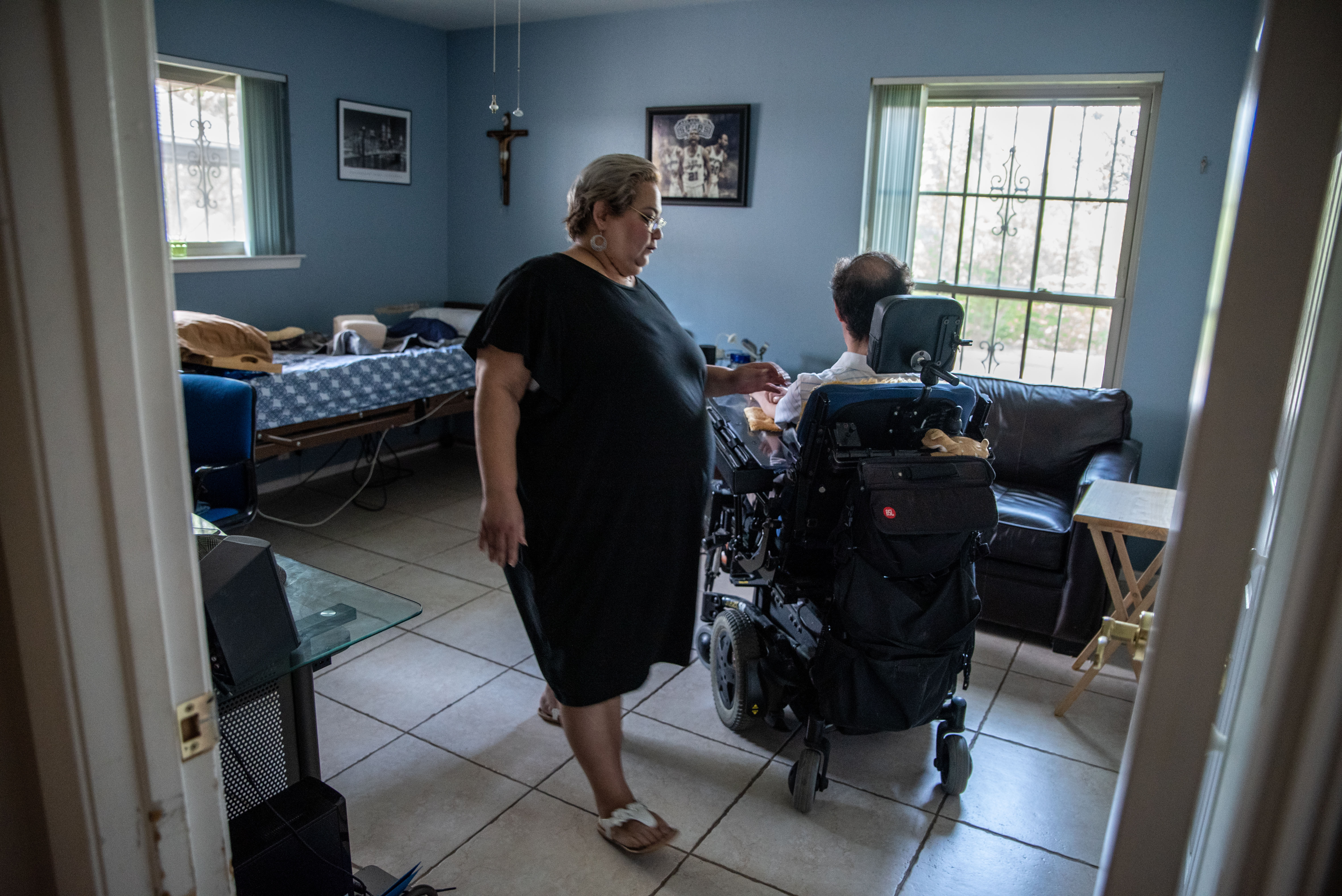 Ramona Cortes helps Gil Vasquez in his home in San Antonio on July 30. Vasquez has muscular dystrophy and receives a lot of care from his father, who was hospitalized after becoming sick with the coronavirus. MUST CREDIT: Photo by Sergio Flores for The Washington Post.