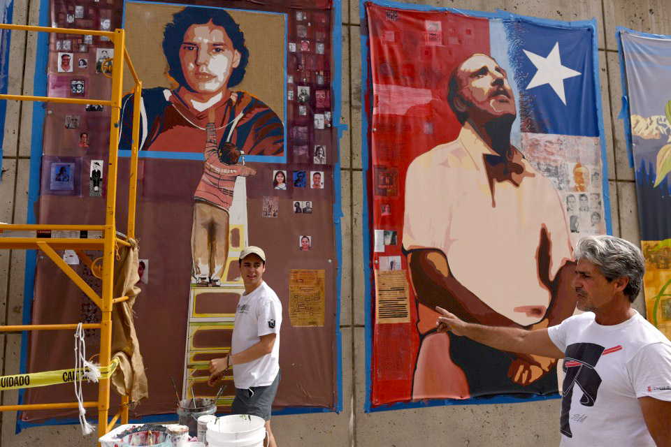 Artist Francisco Letelier, right, directs work on the