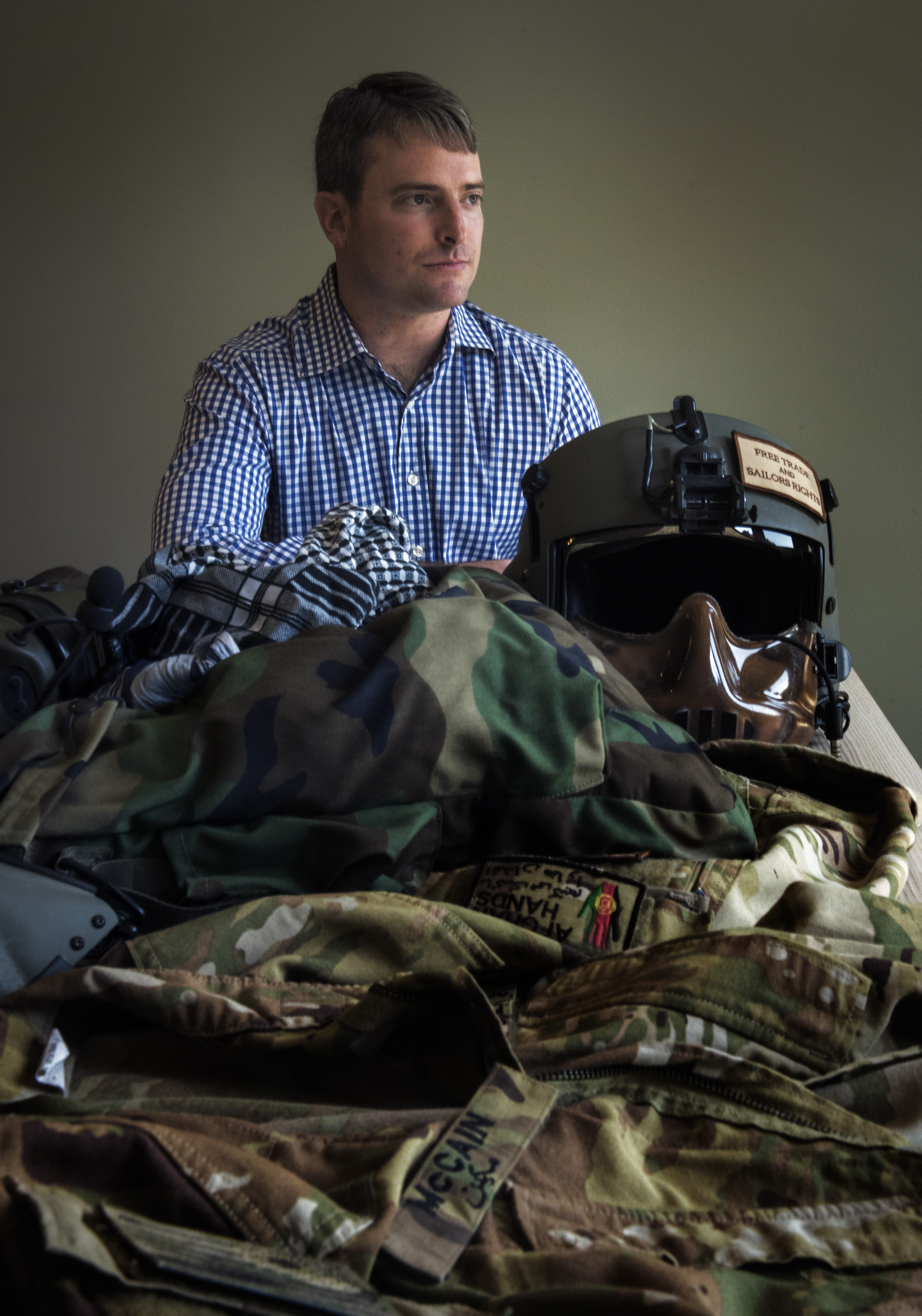 Jack McCain, son of Sen. John McCain, last month at his home in Bethesda, Md., with items that he wore during his service in Afghanistan. MUST CREDIT: Washington Post photo by Bill O'Leary