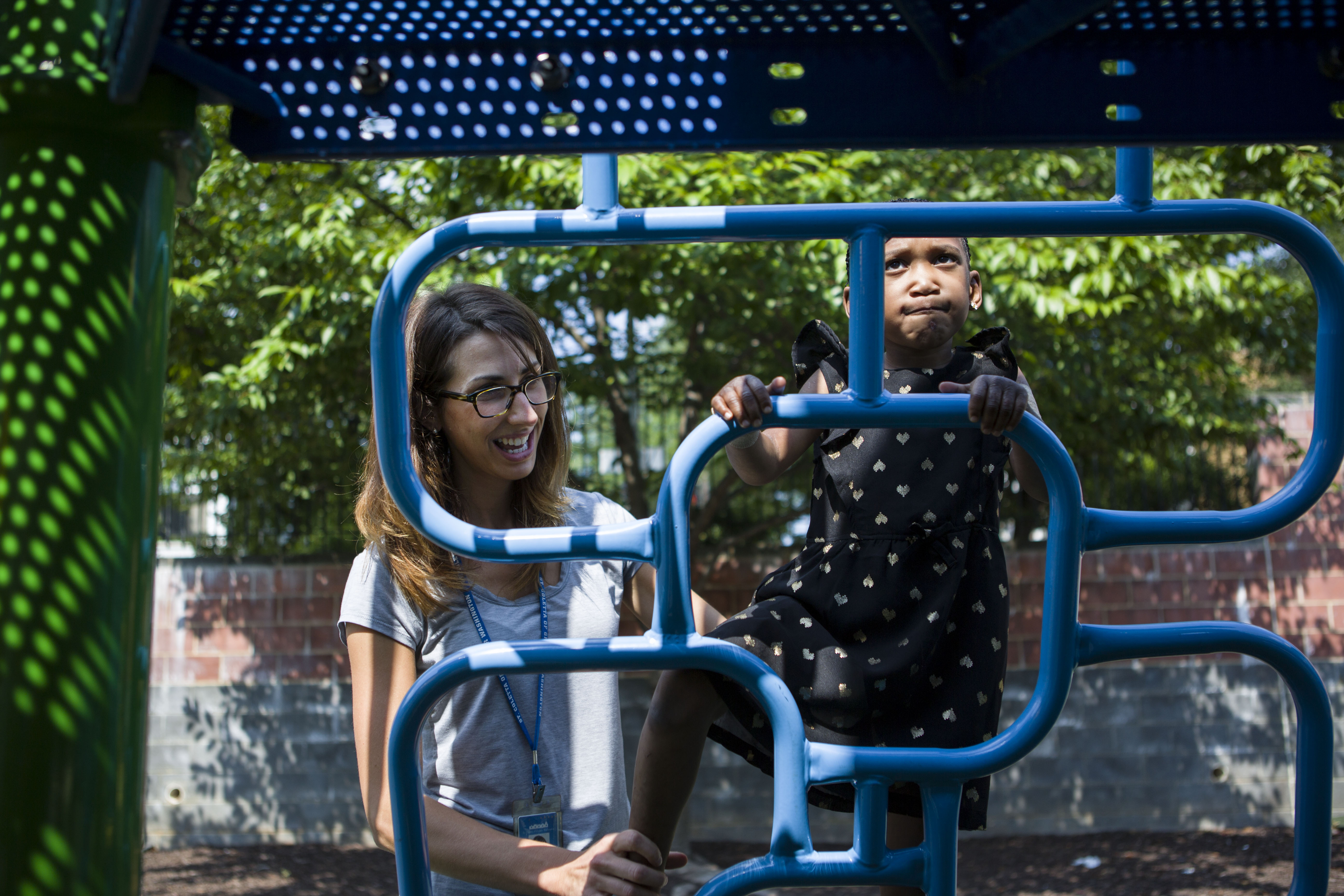 Physical therapist Lauren Fery spots student Kamille Davis as she climbs up the playground ladder at St. Coletta. MUST CREDIT: Washington Post photo by Calla Kessler.