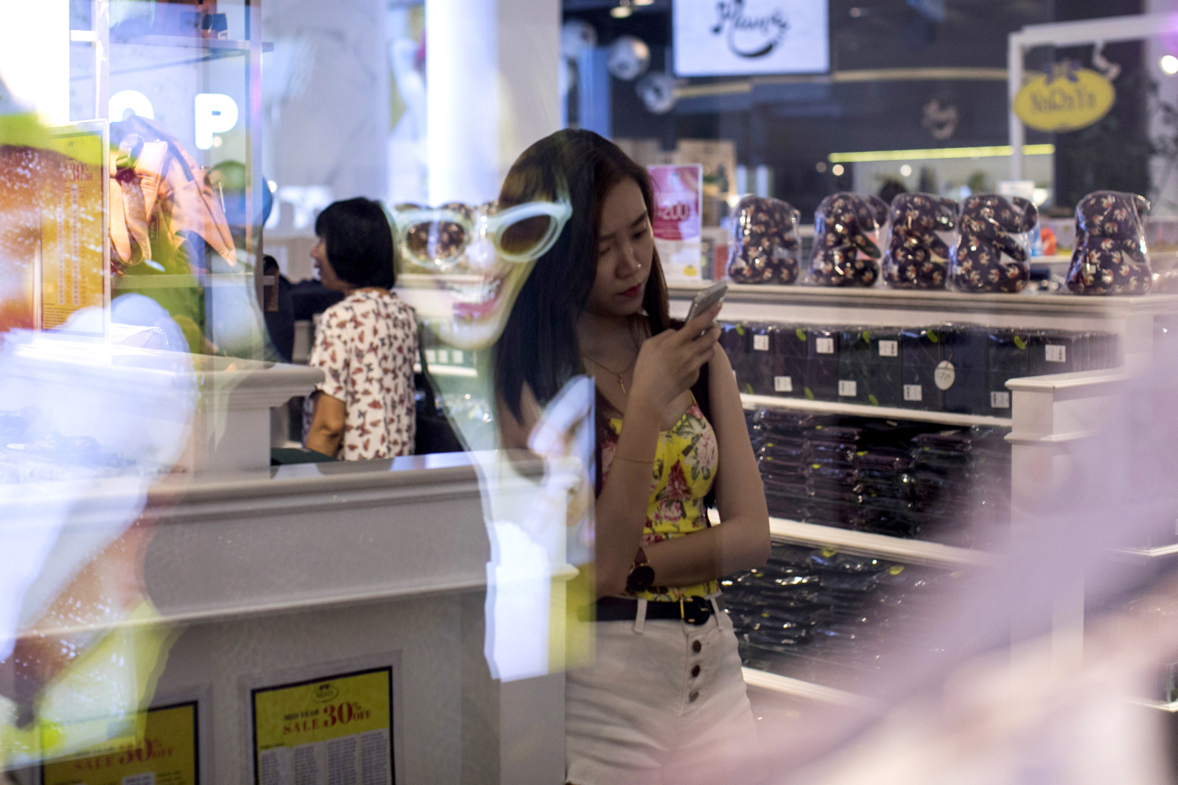 A shopper looks at a smartphone at a mall in Bangkok, Thailand, on Saturday, June 16, 2018. By 2020, more than half of the world's population will be
