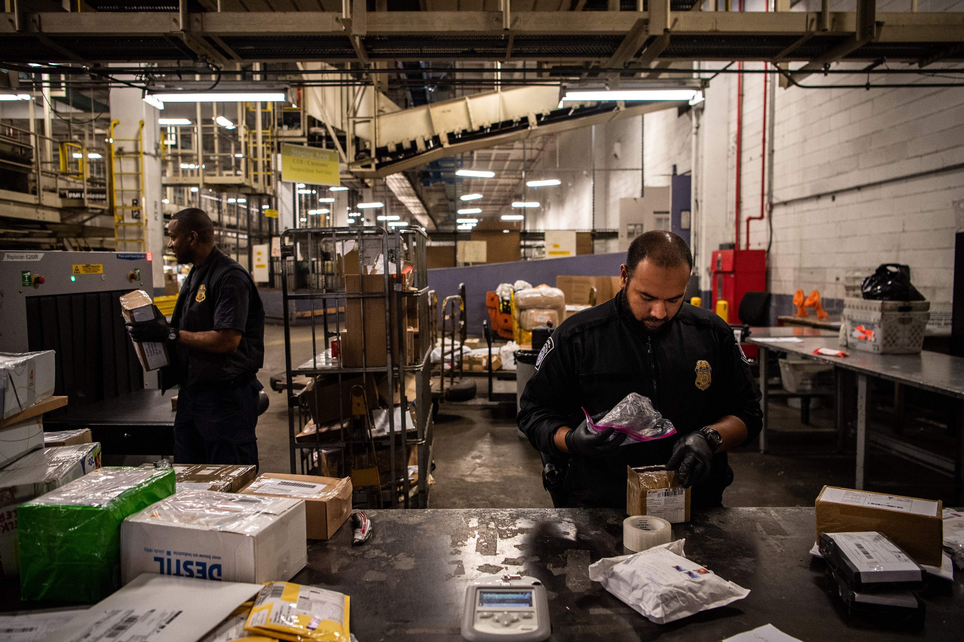 Sustoms and Border Protection officer Mohammed Rahman holds a bag later found to be filled with fentanyl at John F. Kennedy International Airport's mail facility in New York on Sept. 7, 2018. MUST CREDIT: Washington Post photo by Salwan Georges