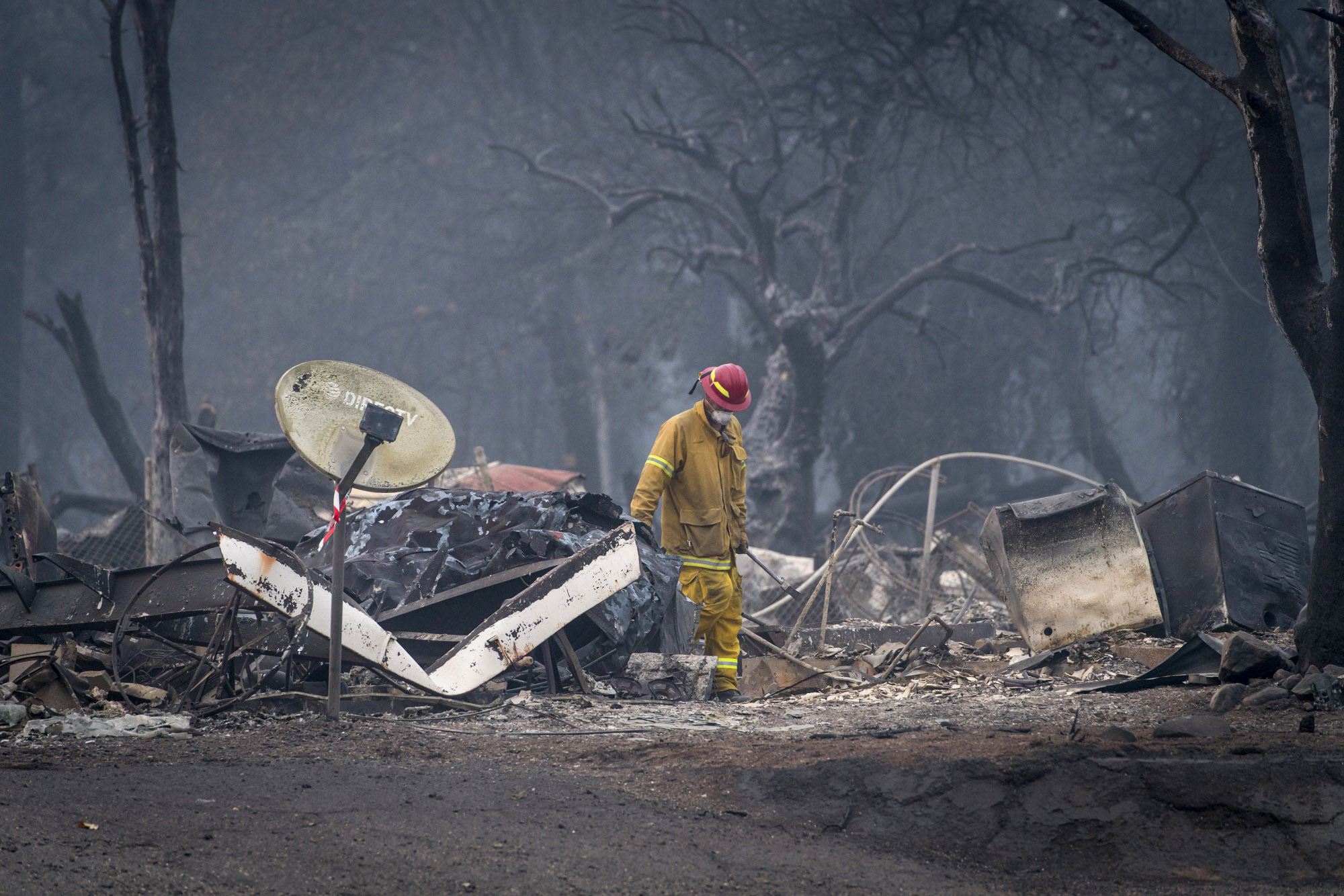 A firefighter searches a burned-out building in Paradise, Calif., on Nov. 15, 2018. MUST CREDIT: Bloomberg photo by David Paul Morris.