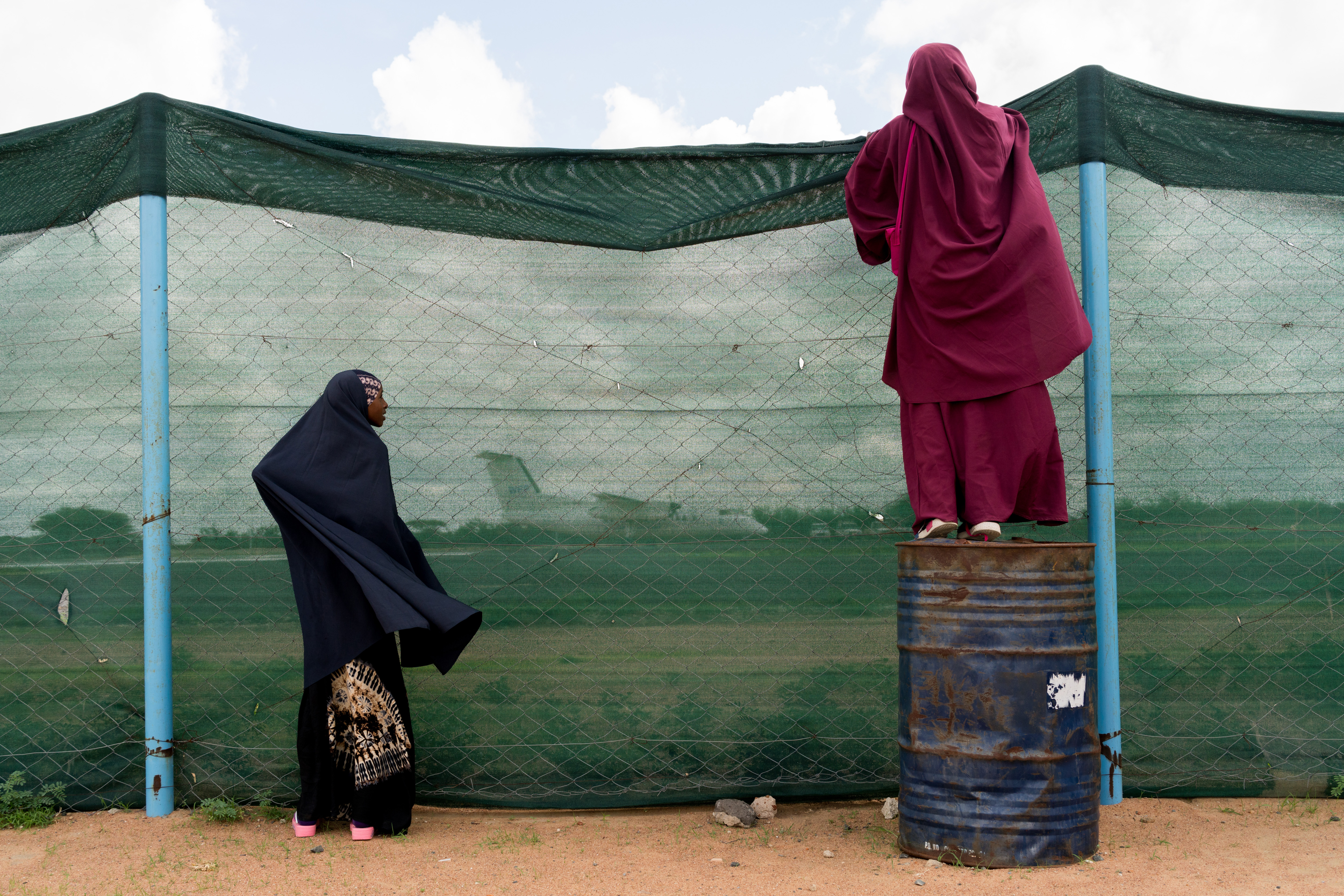 Khairo Hassan's girls watch as their plane lands in Dadaab, Kenya. MUST CREDIT: photo for The Washington Post by Adriane Ohanesian.