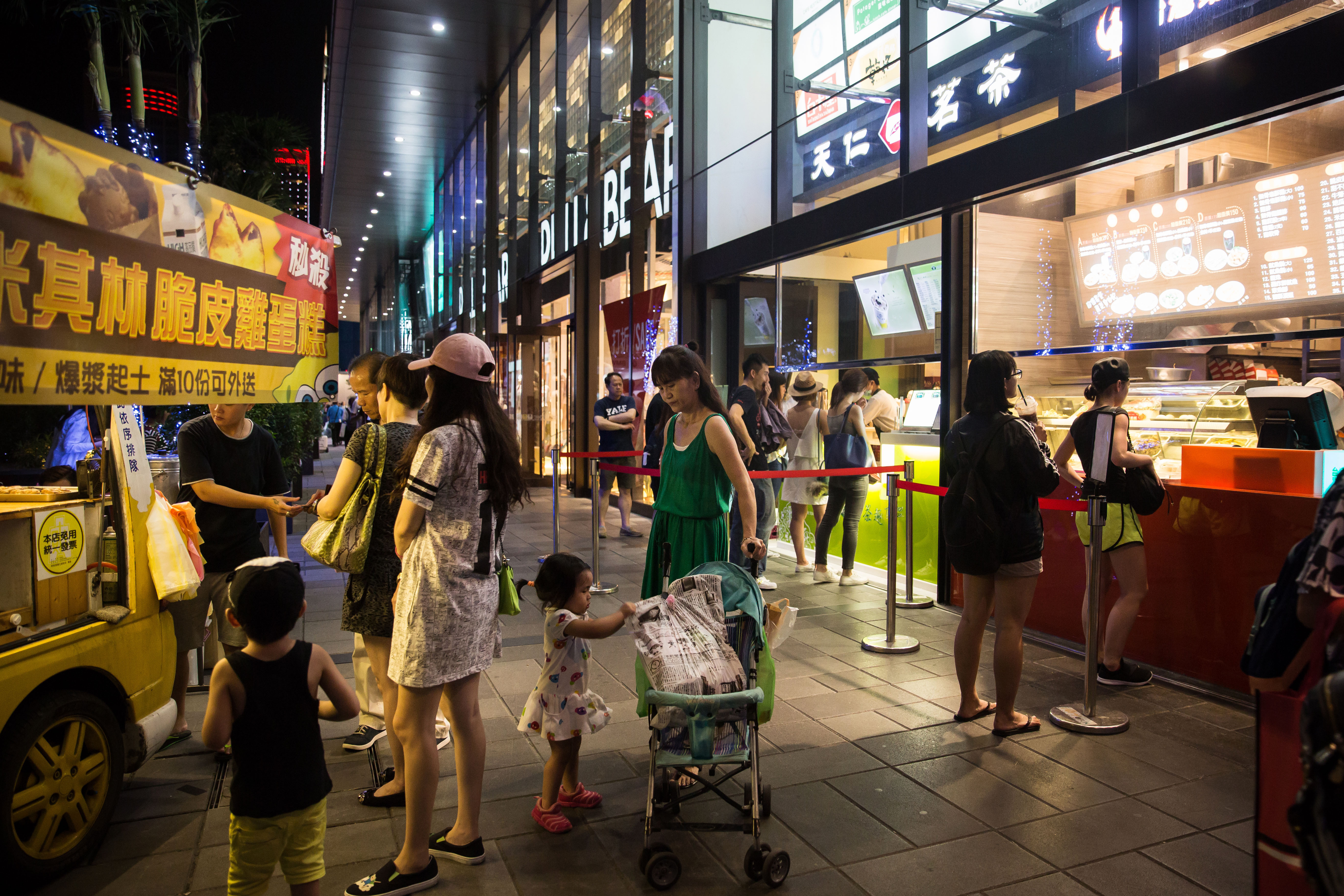 Pedestrians and shoppers wait at food stalls and stores in Taipei, Taiwan, on July 16, 2016. MUST CREDIT: Bloomberg photo by Billy H.C. Kwok.