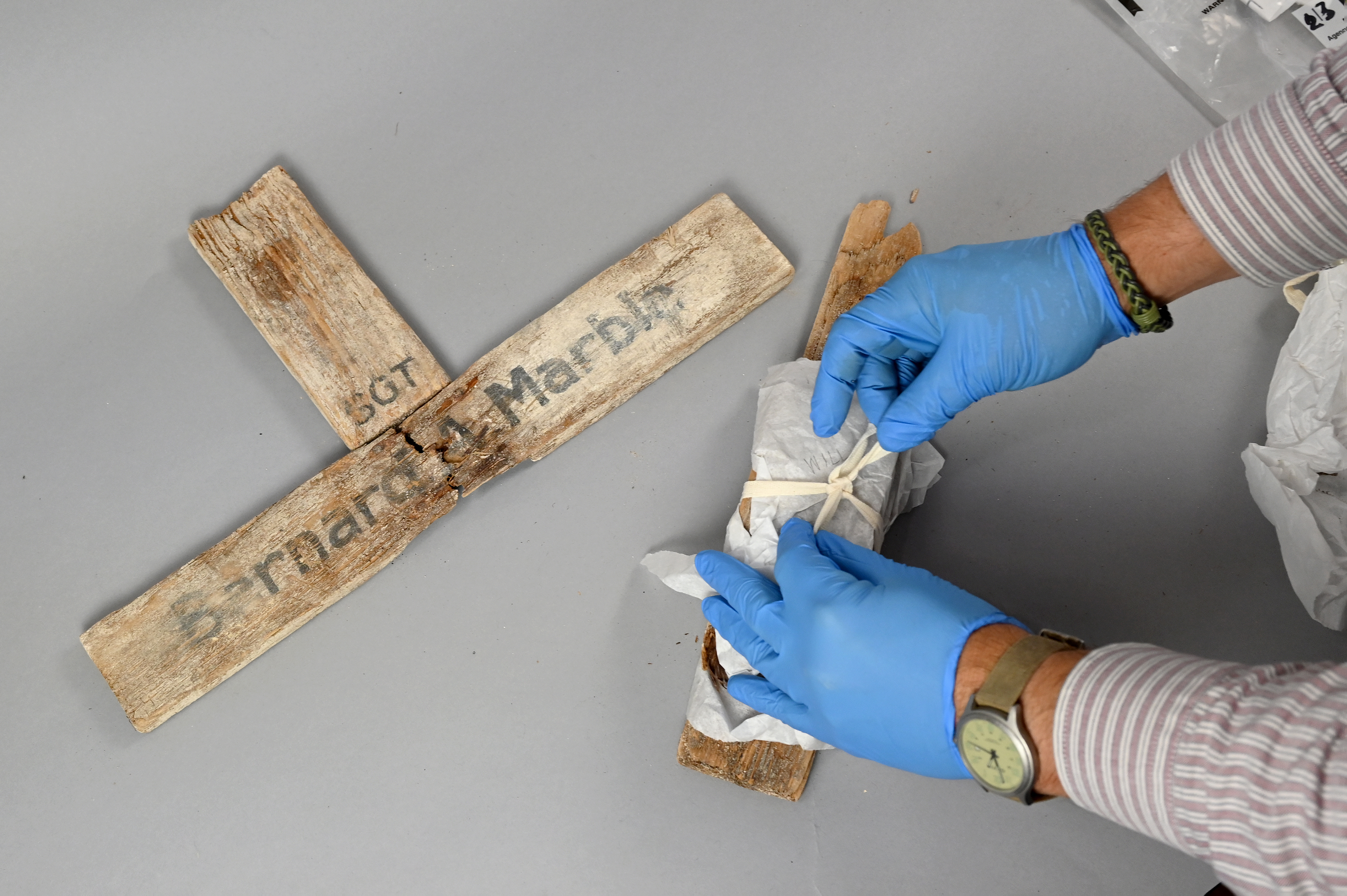 Owen L. Conner, curator for the National Museum of the Marine Corps, unwraps pieces of a wooden cross bearing the name of Sgt. Bernard A. Marble, 28, of Massachusetts, one of more than 1,000 Marines who died in the 1943 battle for Tarawa. MUST CREDIT: Washington Post photo by Katherine Frey.