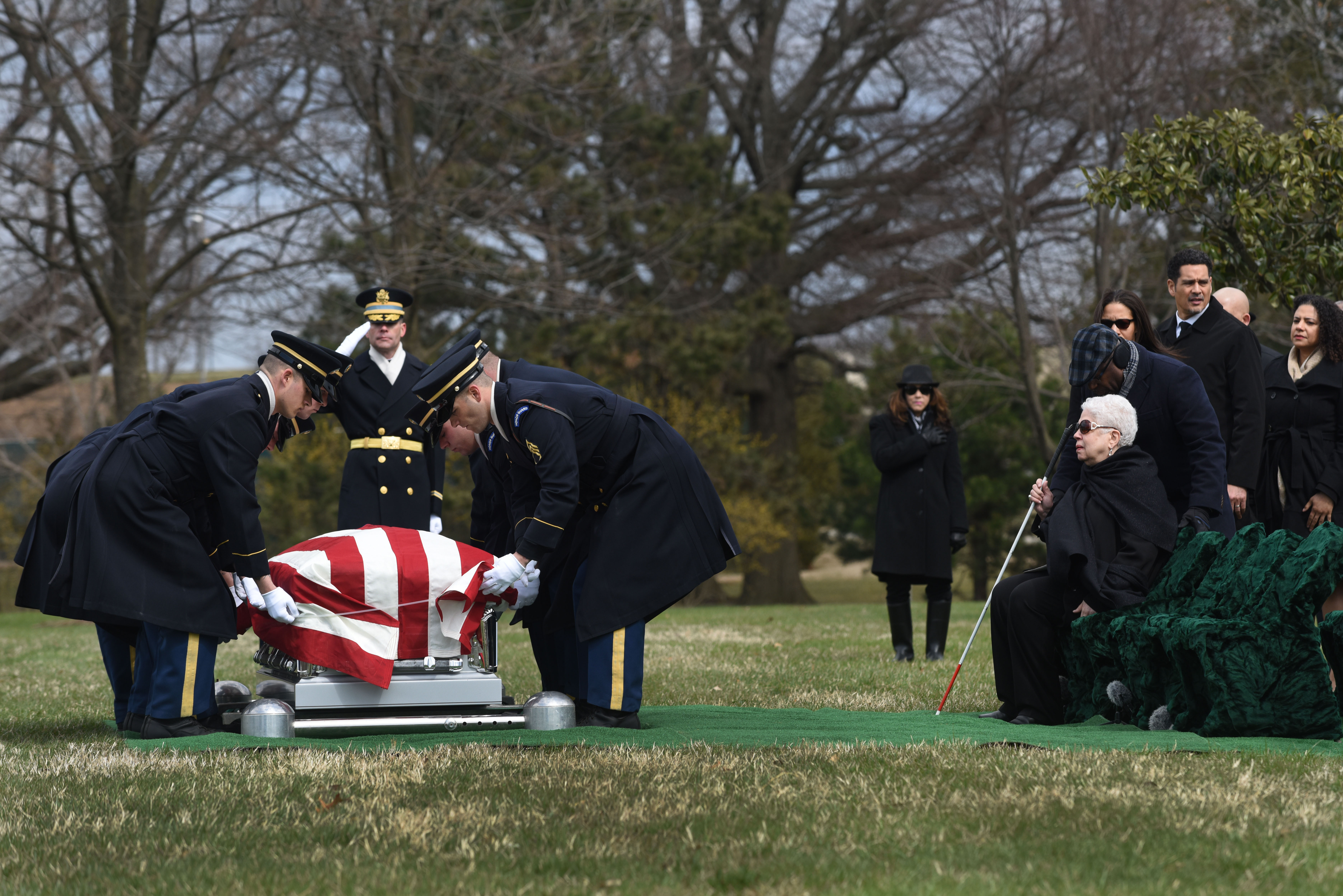 Marla Andrews, right, watches on Friday in Arlington National Cemetery as an honor guard lowers the casket carrying her father, Capt. Lawrence E. Dickson, a Tuskegee Airman whose remains were located in 2017 in Austria. MUST CREDIT: Washington Post photo by Michael Robinson Chavez