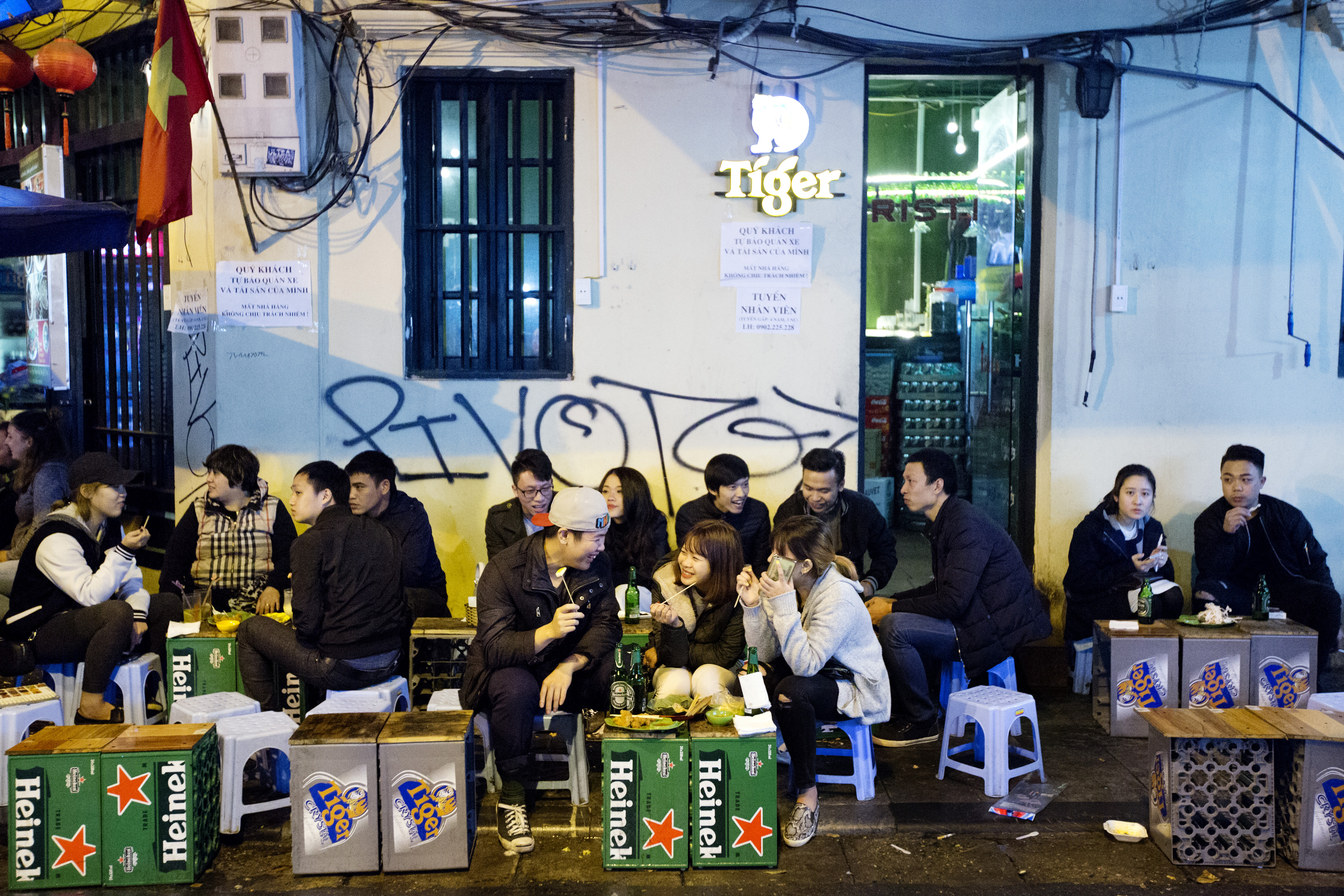 Customers sit eating and drinking over crates featuring branding for Heineken and Tiger beers at an outdoor restaurant in the Old Quarter of Hanoi, Vietnam, on Feb. 22, 2016. MUST CREDIT: Bloomberg photo by Maike Elan.