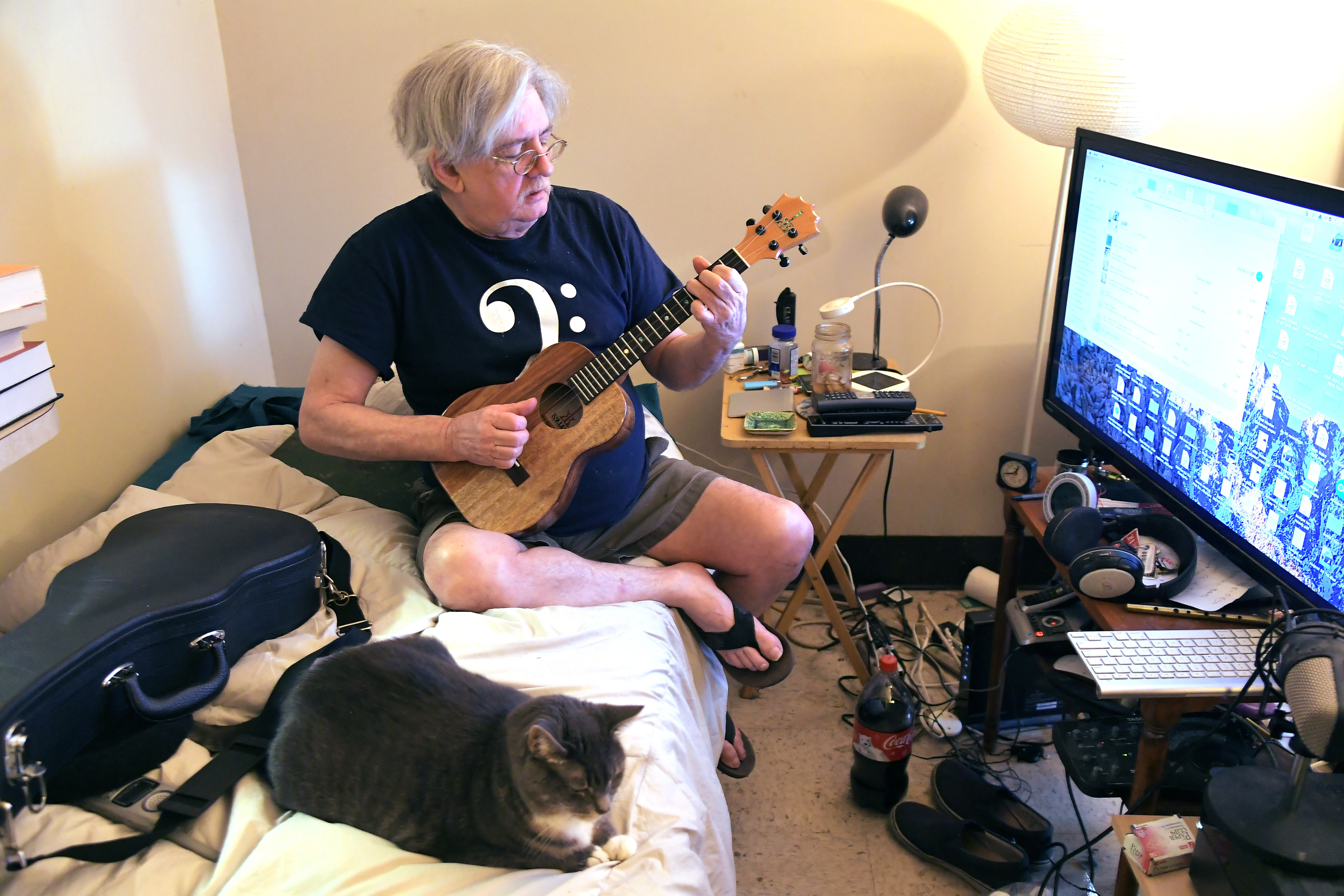 David Weiss, above, who is successfully dealing with several serious menta-lhealth conditions, plays a song he wrote about his sister Faith while his cat, Bab-Babes, rests close by in Weiss's one-bedroom apartment in Frederick, Maryland. Way Station provided Weiss with the apartment as well as a case manager. Must credit: Washington Post photo by Katherine Frey