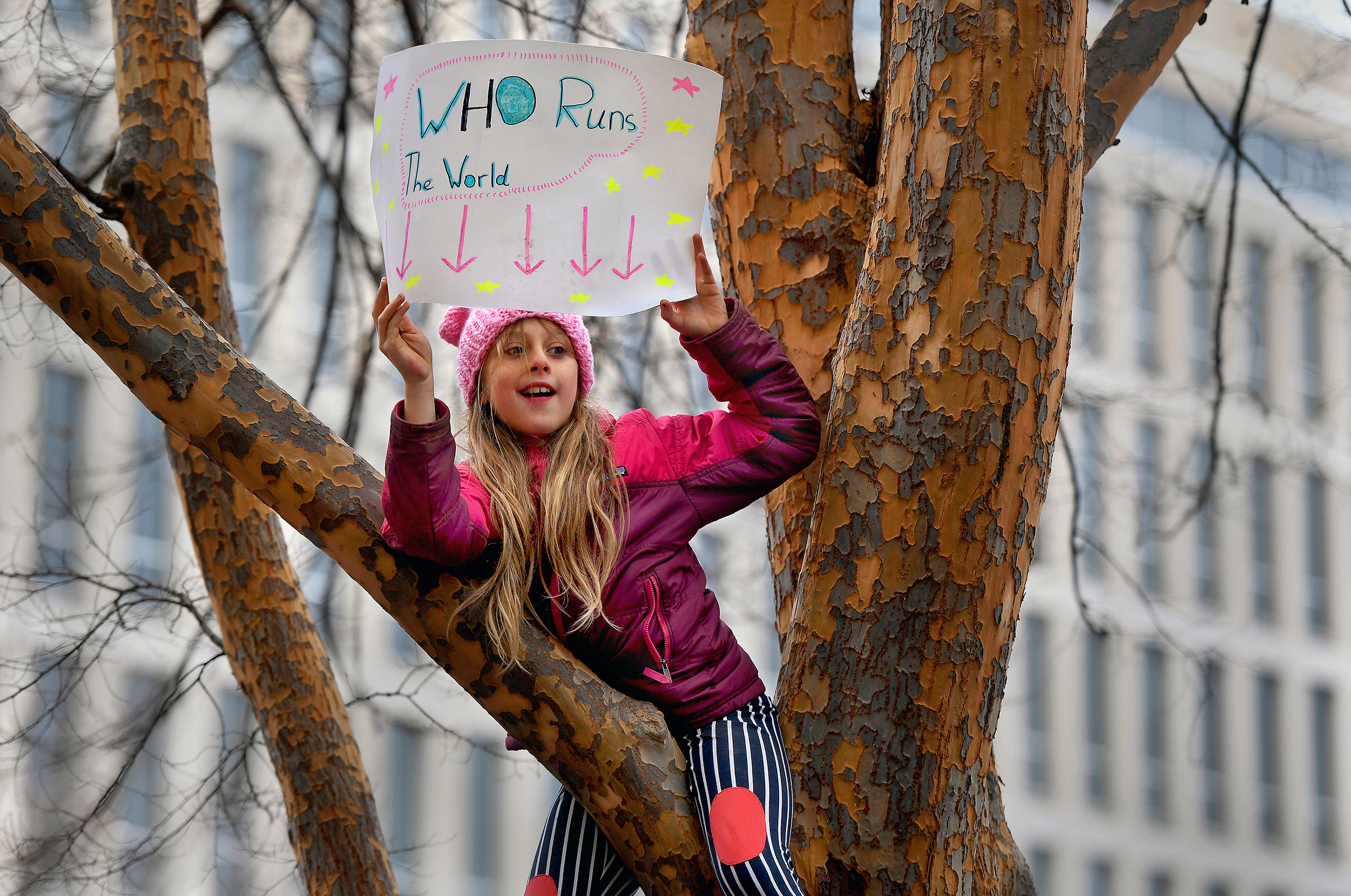 Erin Moskowitz, 9, of Pelham, N.Y., who attended the Women's March on Washington with her parents, grandmother and three sisters, finds a perch from which to view the crowd at the Mall. Must credit: Washington Post photo by Michael S. Williamson